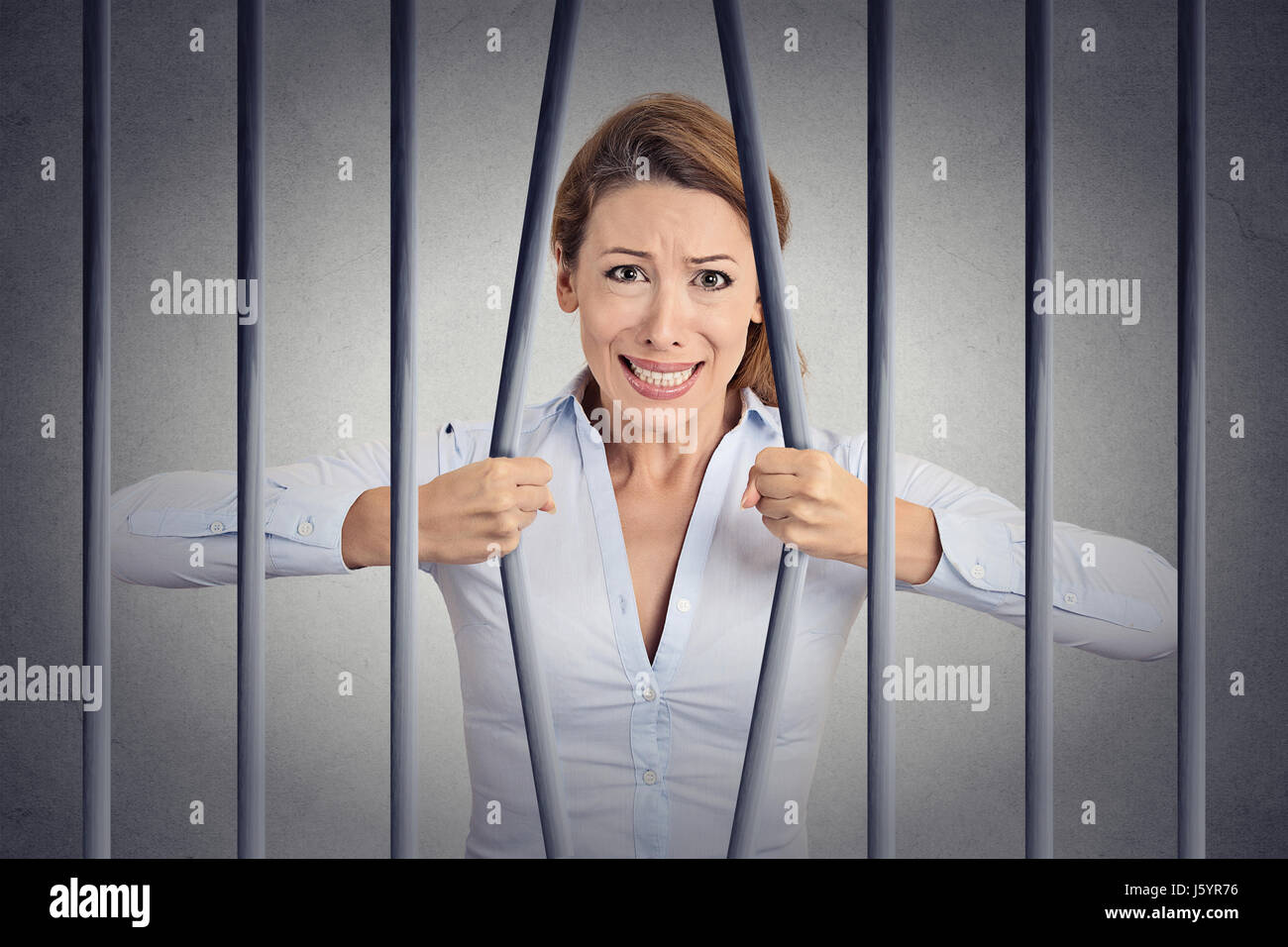 Stressed desperate angry businesswoman bending bars of her prison cell grey wall background. Life limitations, law - Stock Image