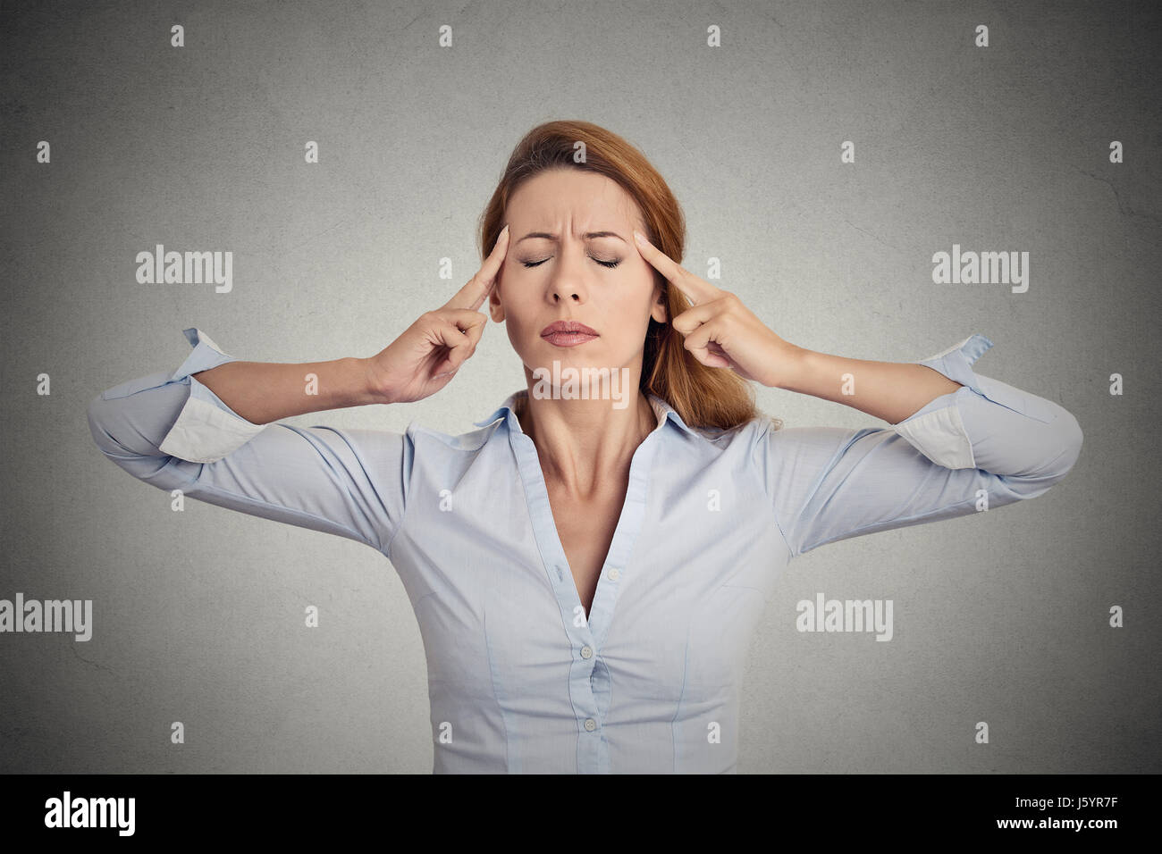 Portrait of concentrating woman isolated on grey wall background. - Stock Image
