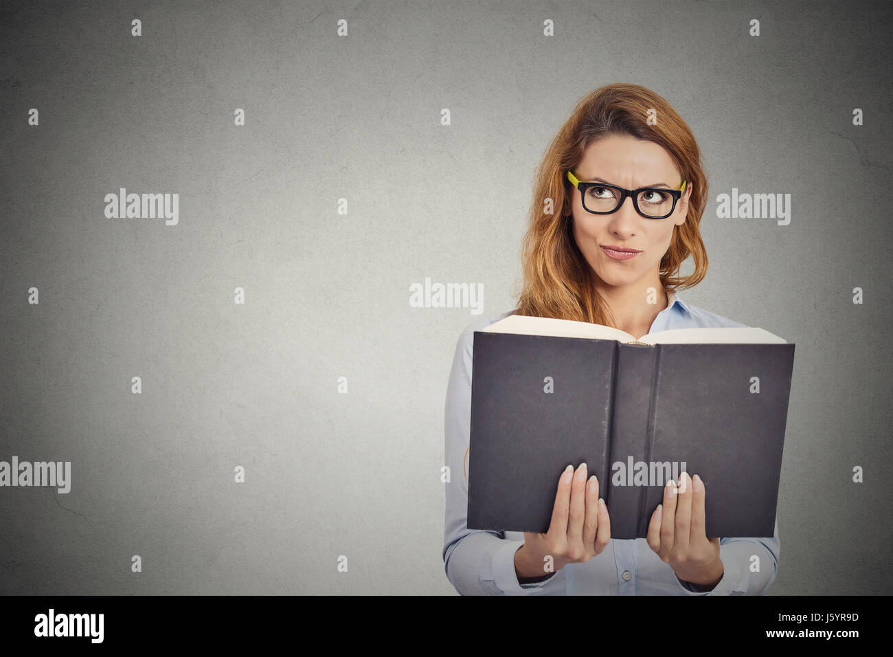 Closeup clever woman reading book having thought isolated on grey wall background. Human face expression - Stock Image