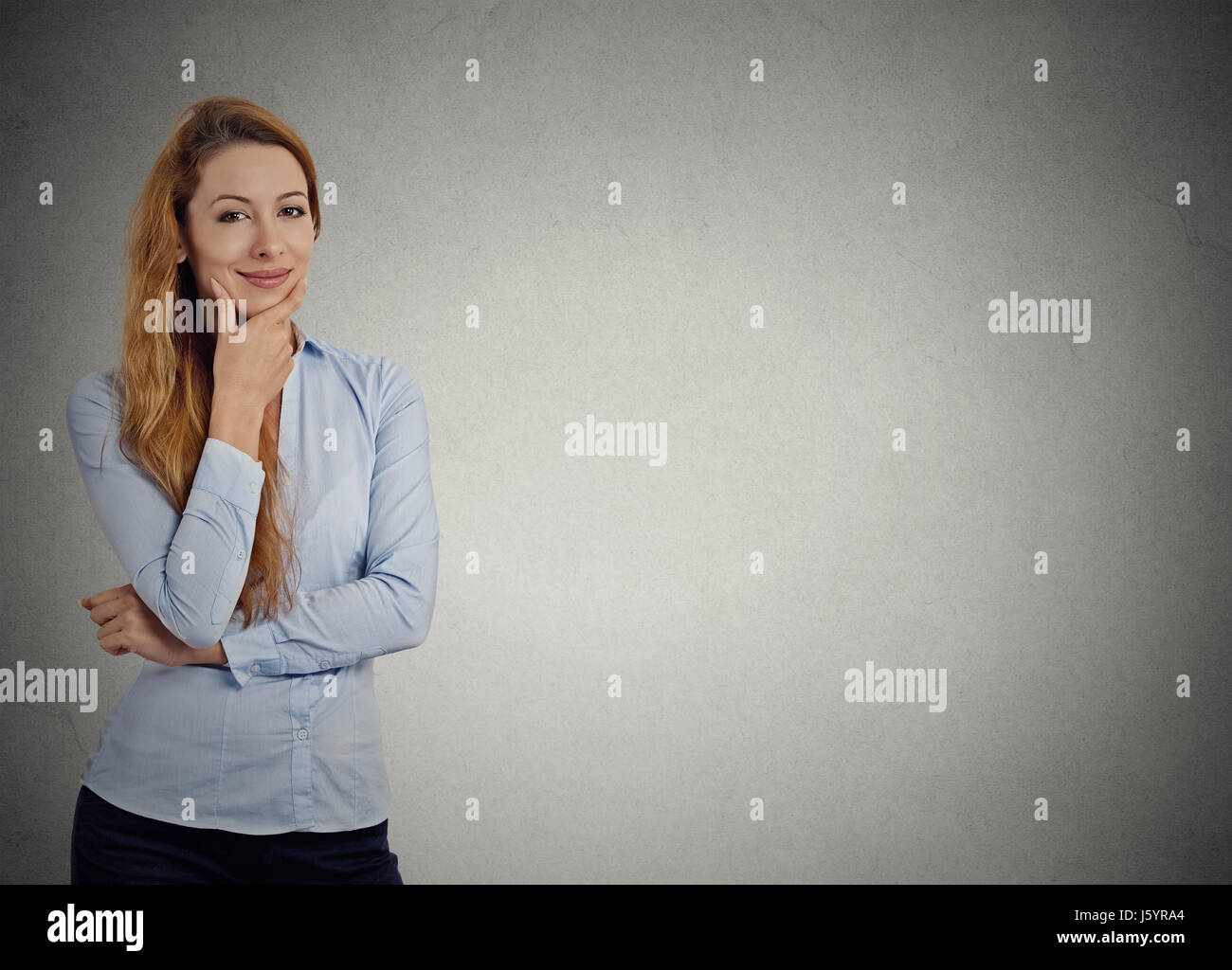 Portrait happy beautiful confident smiling woman thinking looking at camera isolated grey wall background with copy - Stock Image