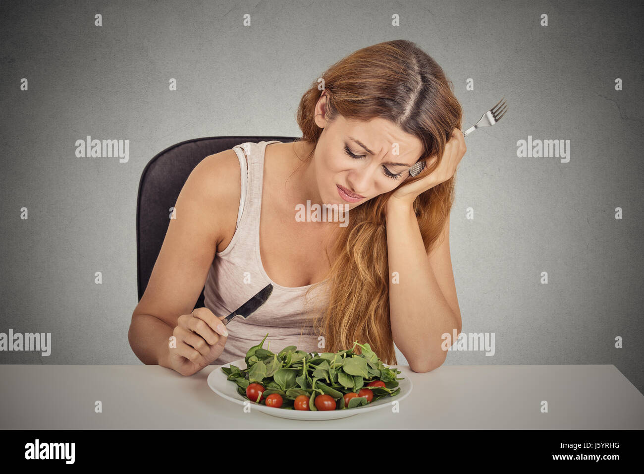 sad displeased young woman eating salad isolated grey wall background. Negative human face expression emotion. - Stock Image