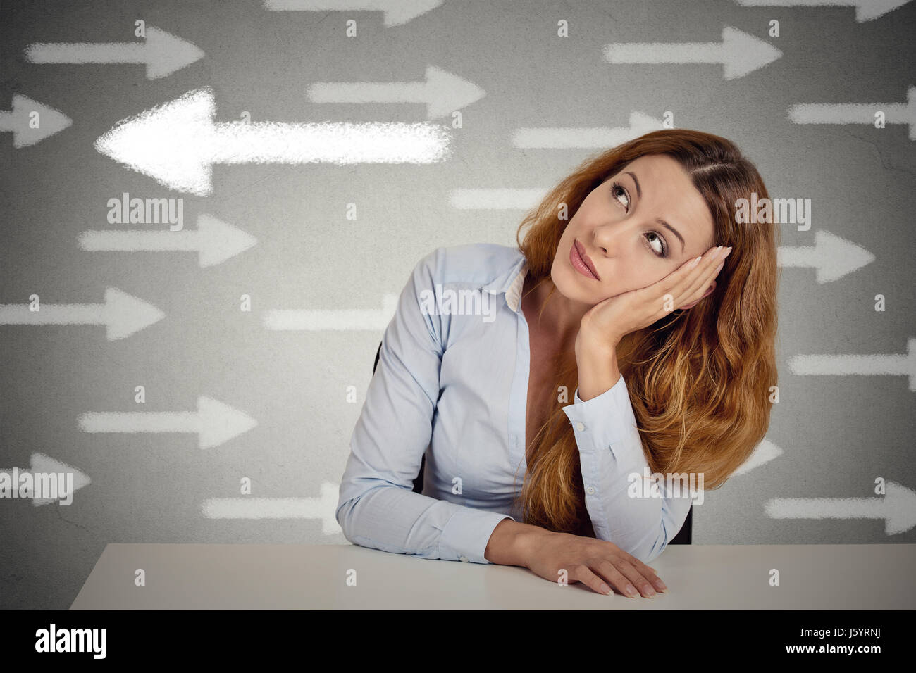 Thoughtful woman taking a chance going against flow. Thoughtful businesswoman sitting at table isolated on grey - Stock Image