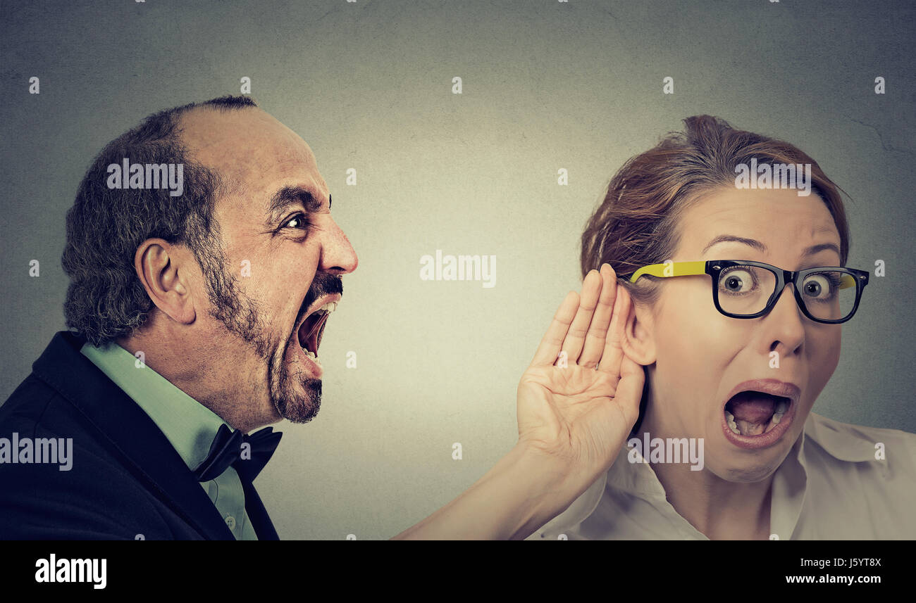 Can you hear me? Portrait angry man screaming curious surprised woman with glasses and hand to ear gesture listens - Stock Image