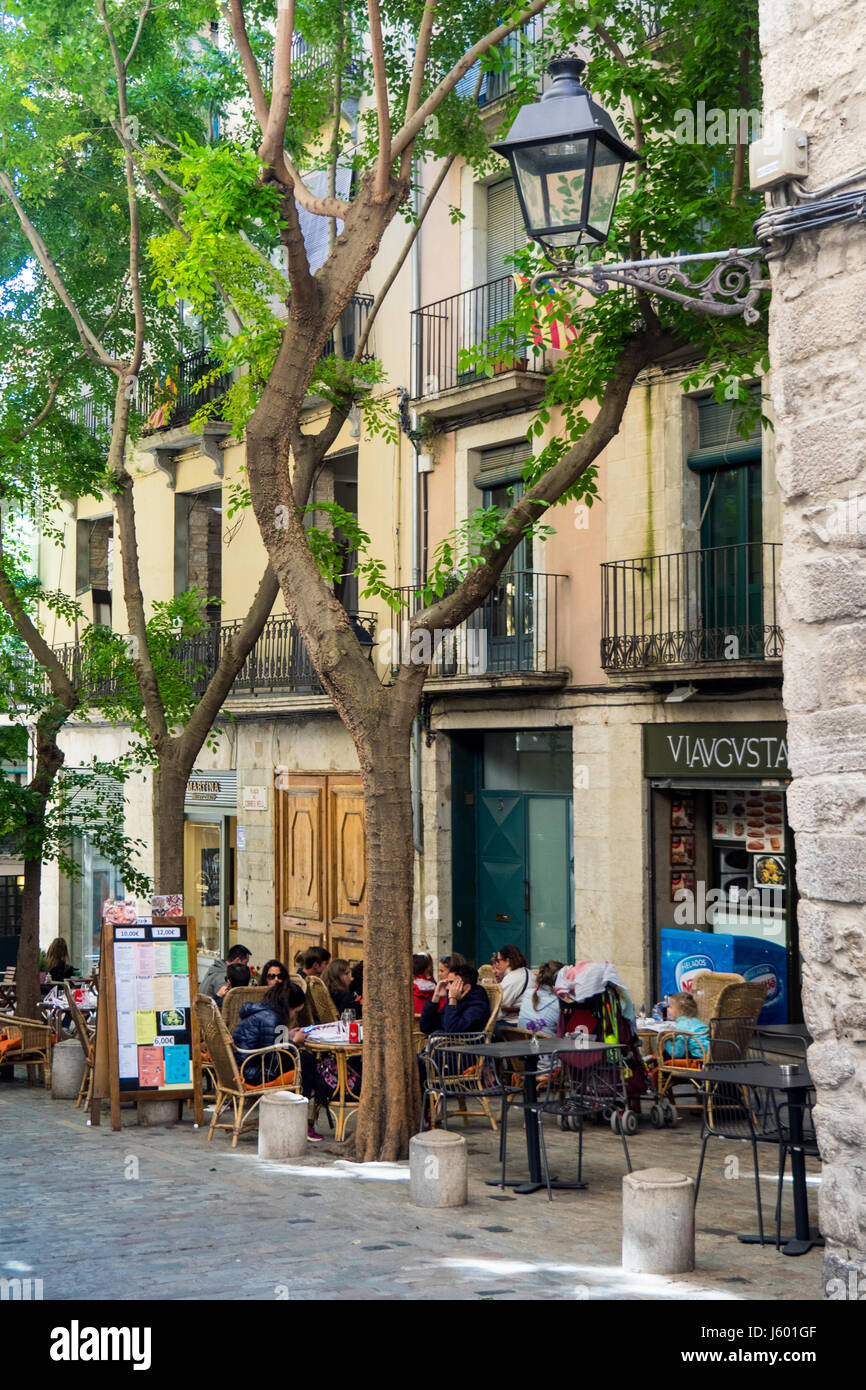 Diners eating al fresco style in the old quarter of Girona, Spain. - Stock Image