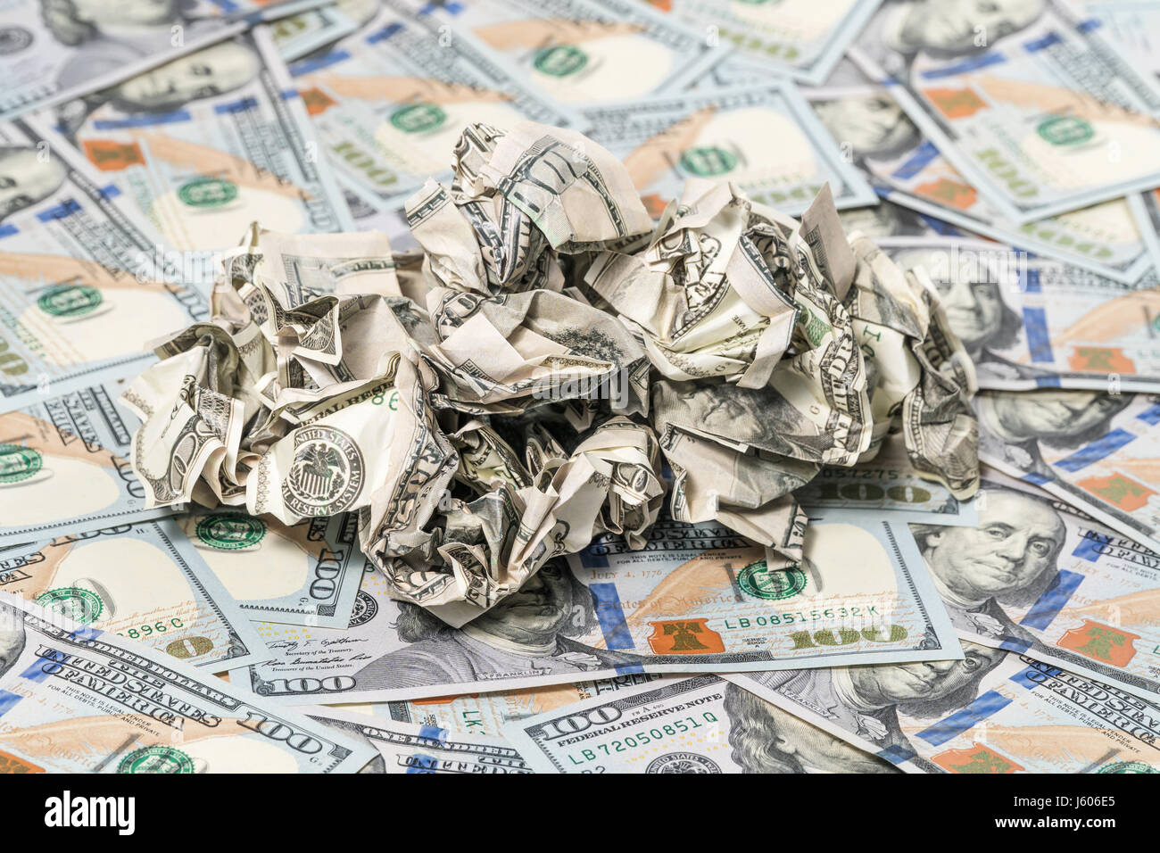 Pile of crumpled money on a background of hundred-dollar bills Stock Photo