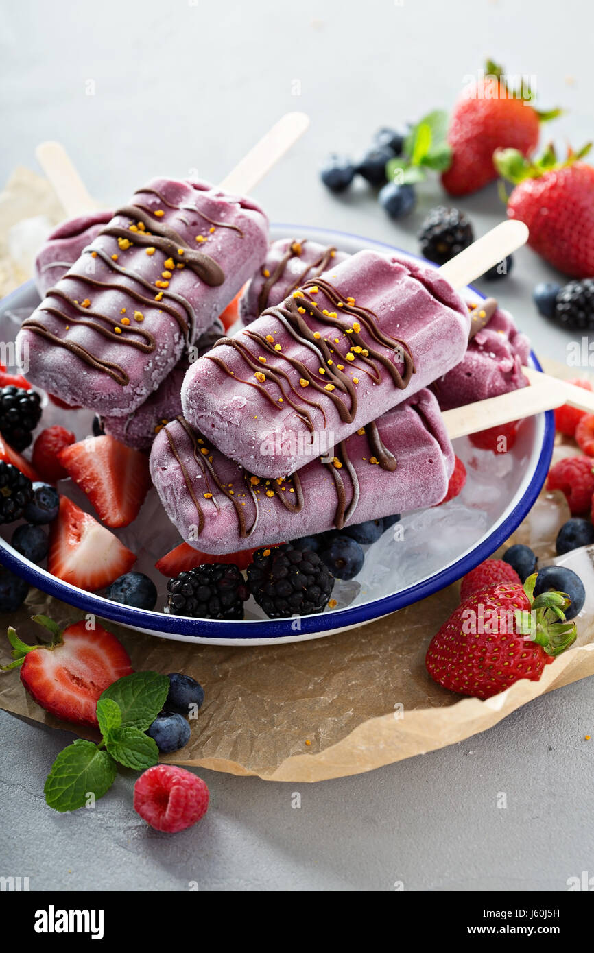 Mixed berry popsicles with chocolate glaze - Stock Image