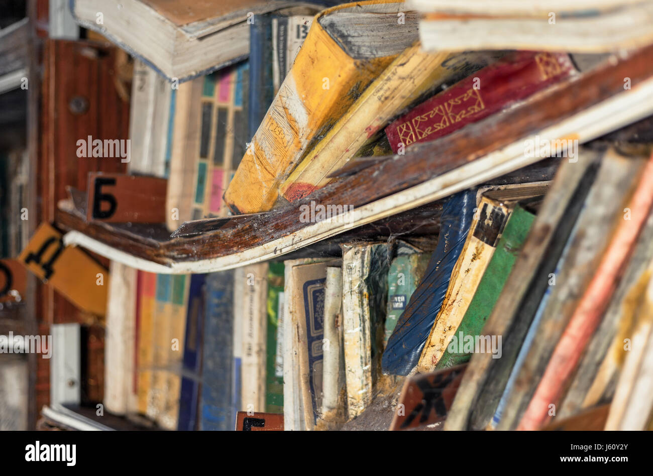 The bent shelf with old dampened books in an abandoned library. Focus on the center of the frame, shallow depth Stock Photo