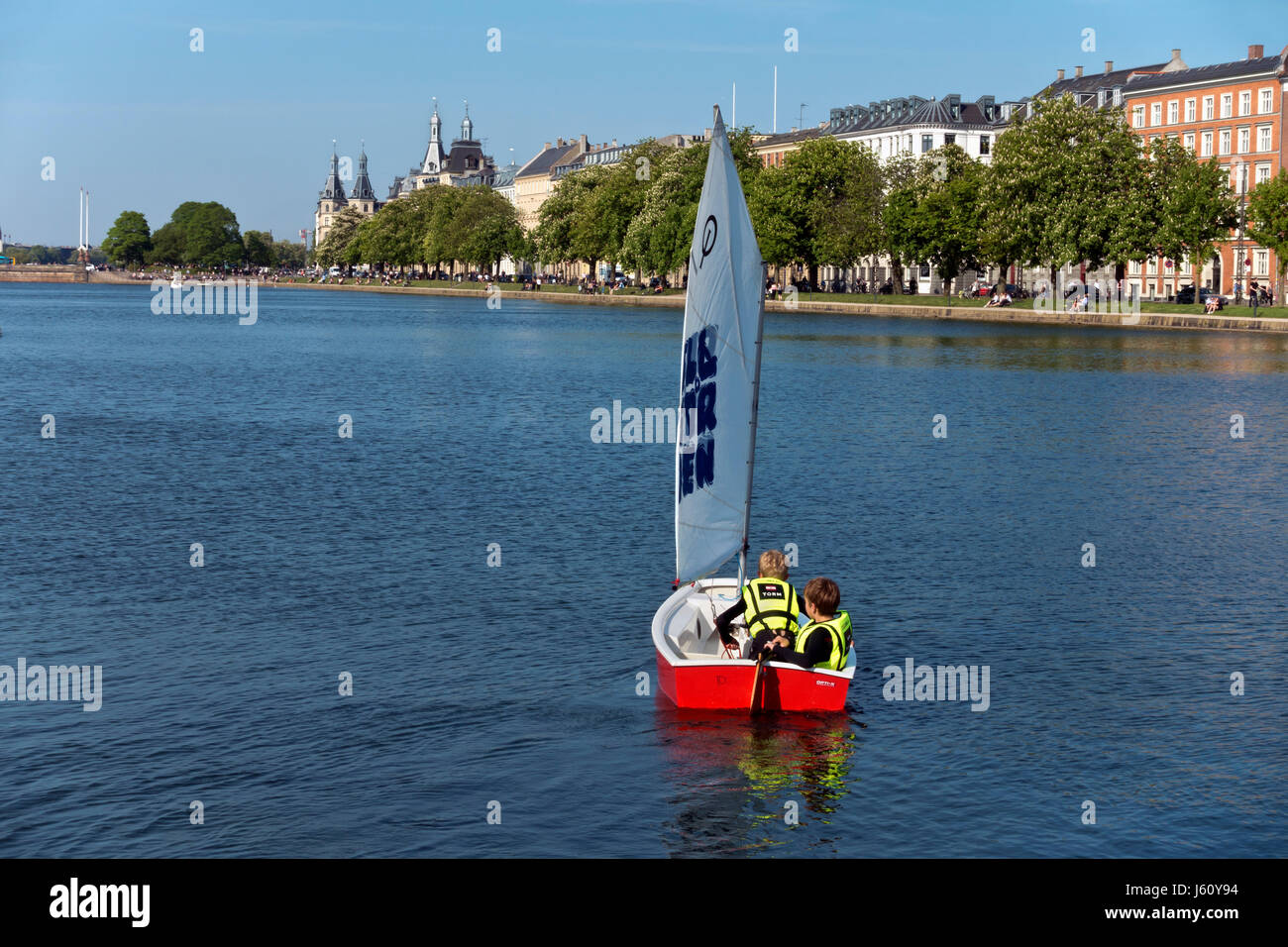 Two boys sailing in an optimist dinghy on the Peblinge Lake in central Copenhagen on a sunny afternoon in early - Stock Image