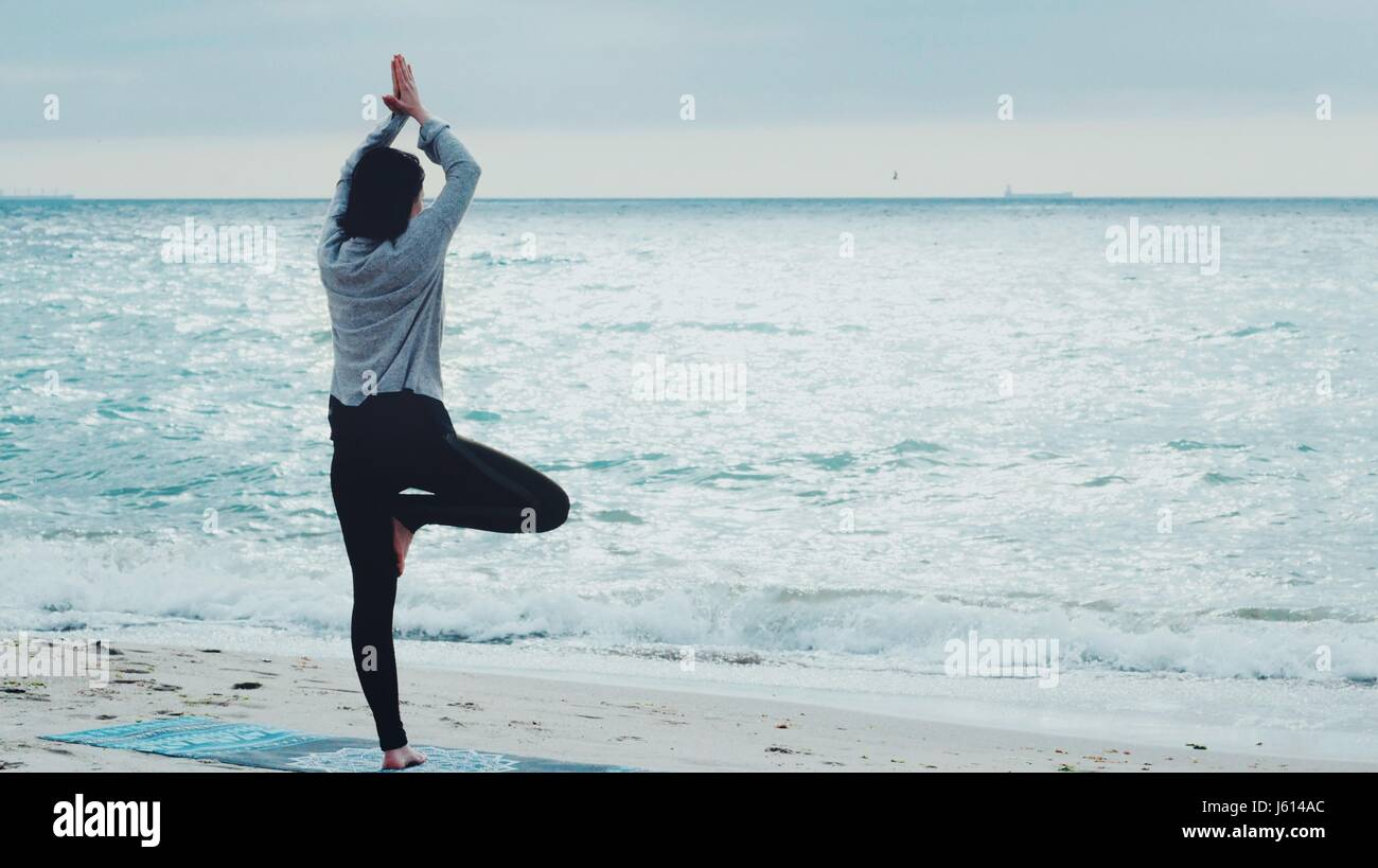 Woman Standing A Grateful Namaste Yoga Pose On The Beach Next To The