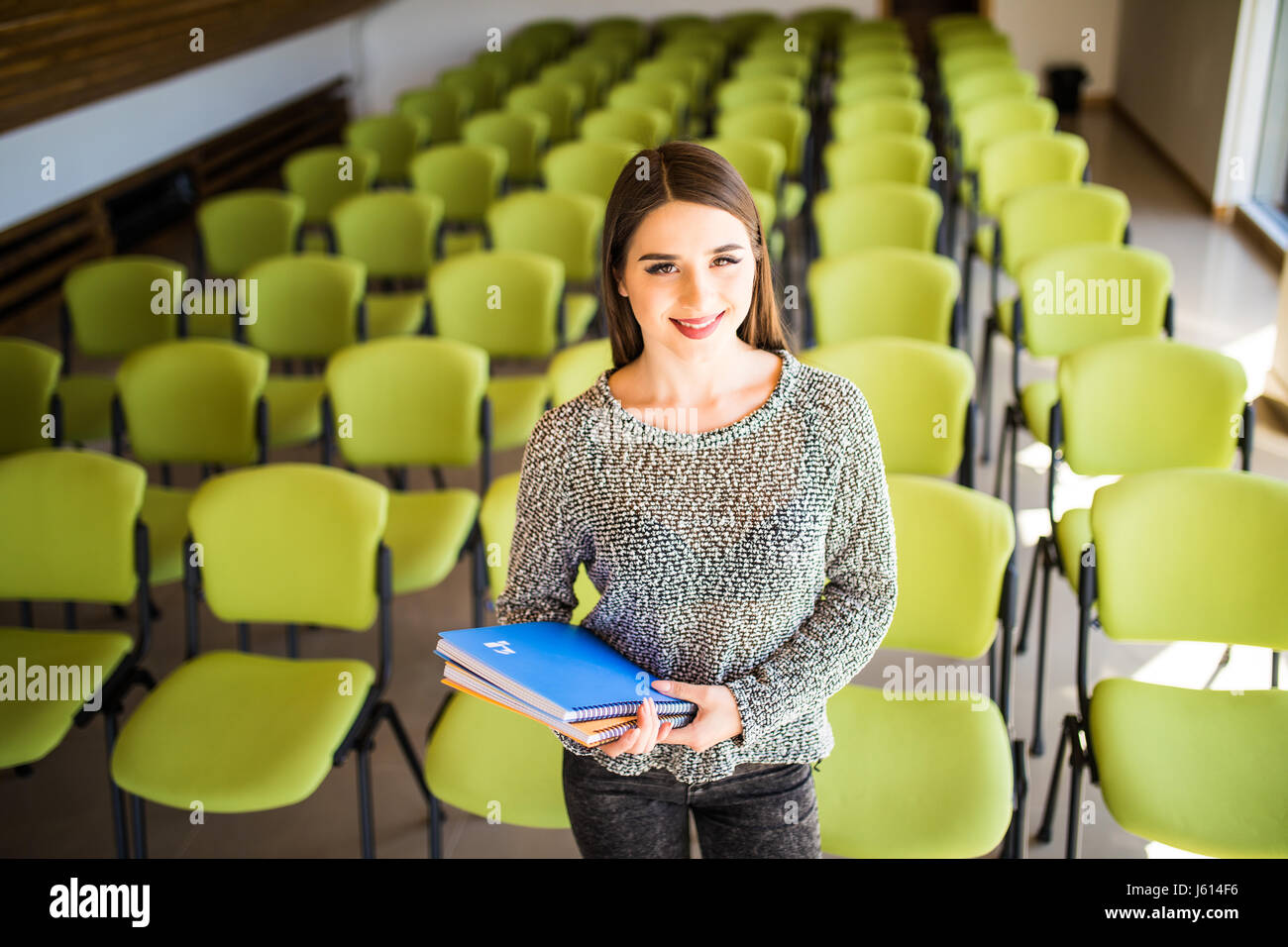 A beautiful business woman sitting alone in an auditorium - Stock Image