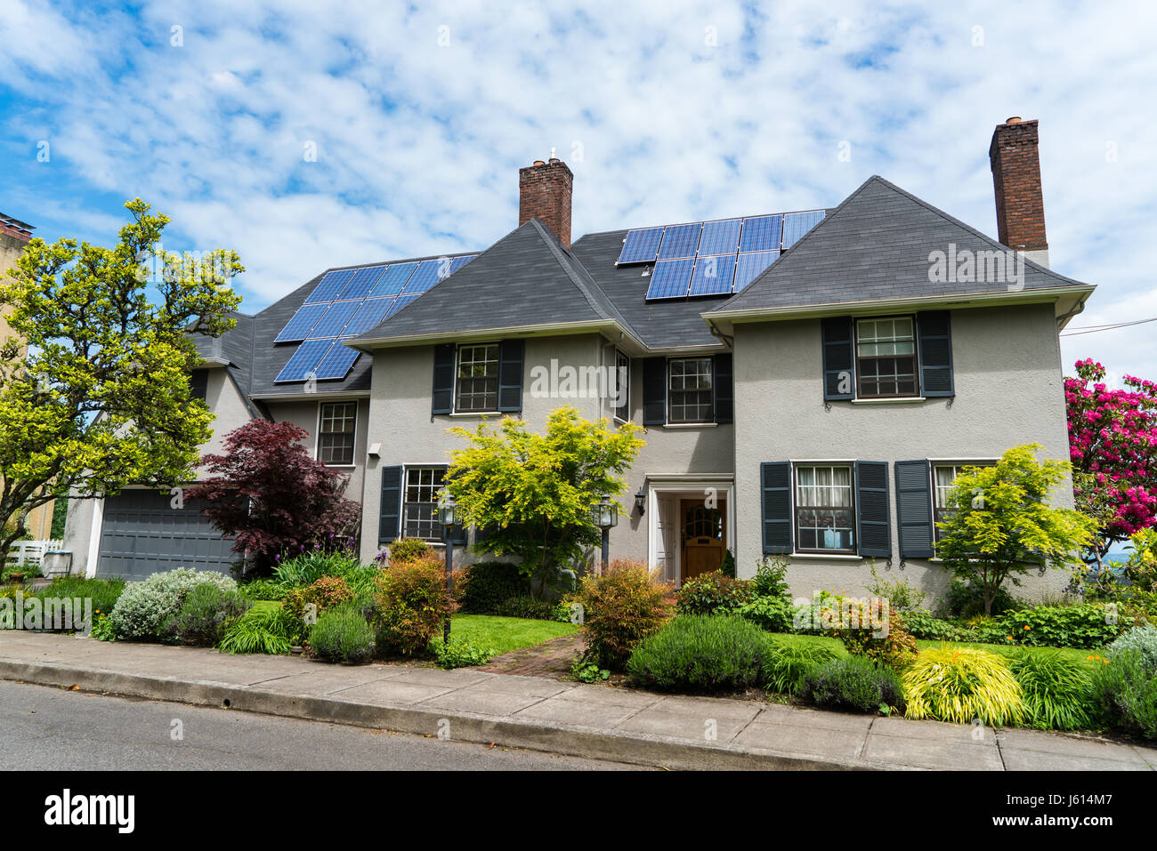Two-story stucco house with solar panels on the roof and nice landscaping - Stock Image