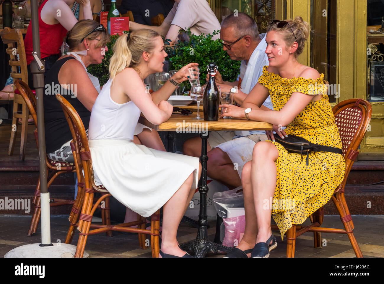 Female friends having a conversation at an Italian restaurant on Mulberry Street in Little Italy in New York City - Stock Image