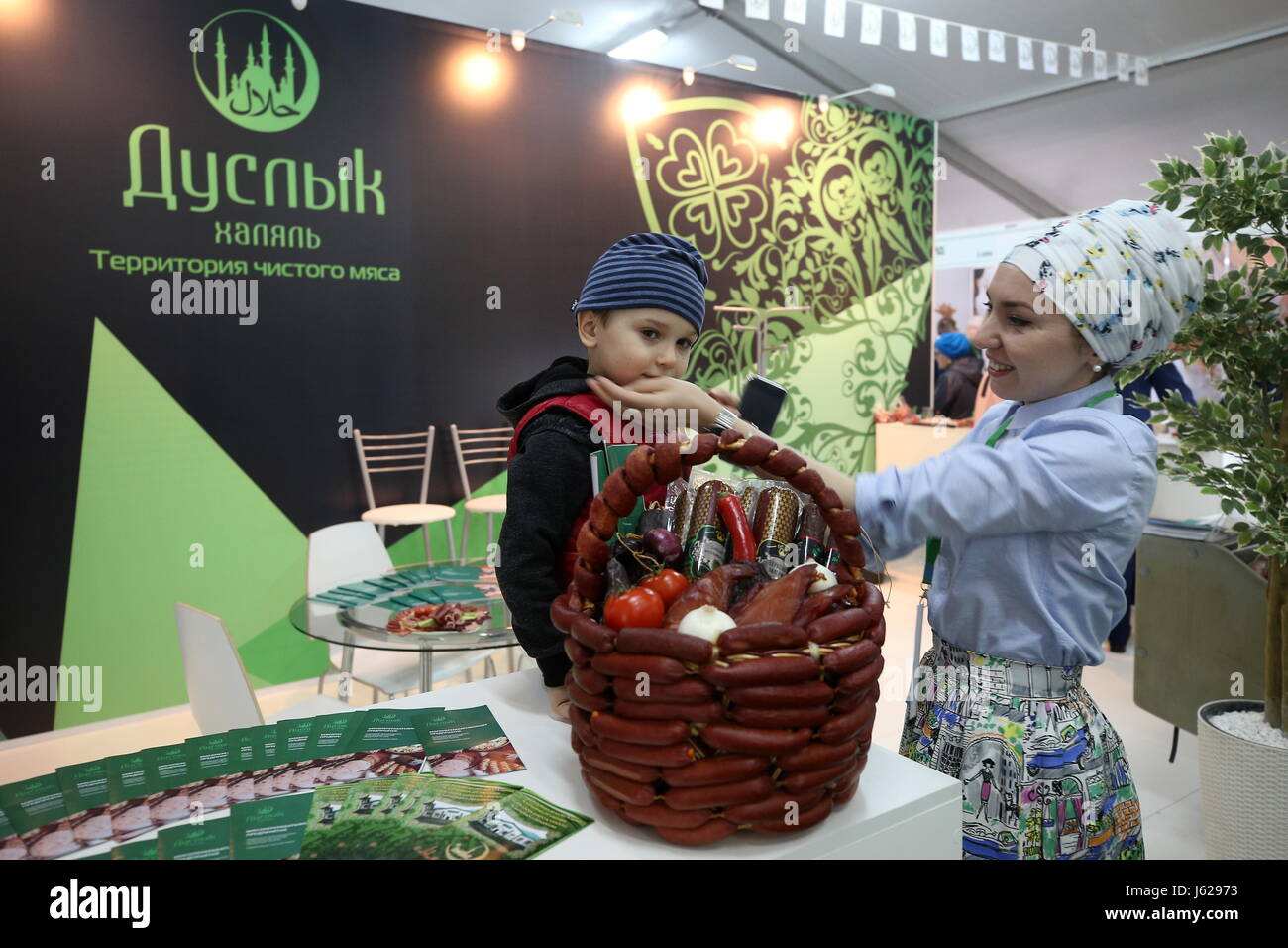 Kazan, Russia. 18th May, 2017. A woman with a child at the Duslyk stand at the Russia Halal Expo exhibition as part - Stock Image