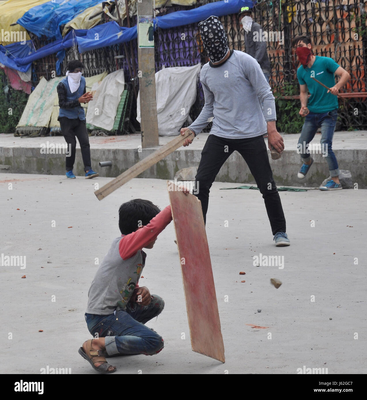 Srinagar, Kashmir. 19th May, 2017. Young Kashmiri boy uses a plywood for sheild  against stones hurled by security - Stock Image