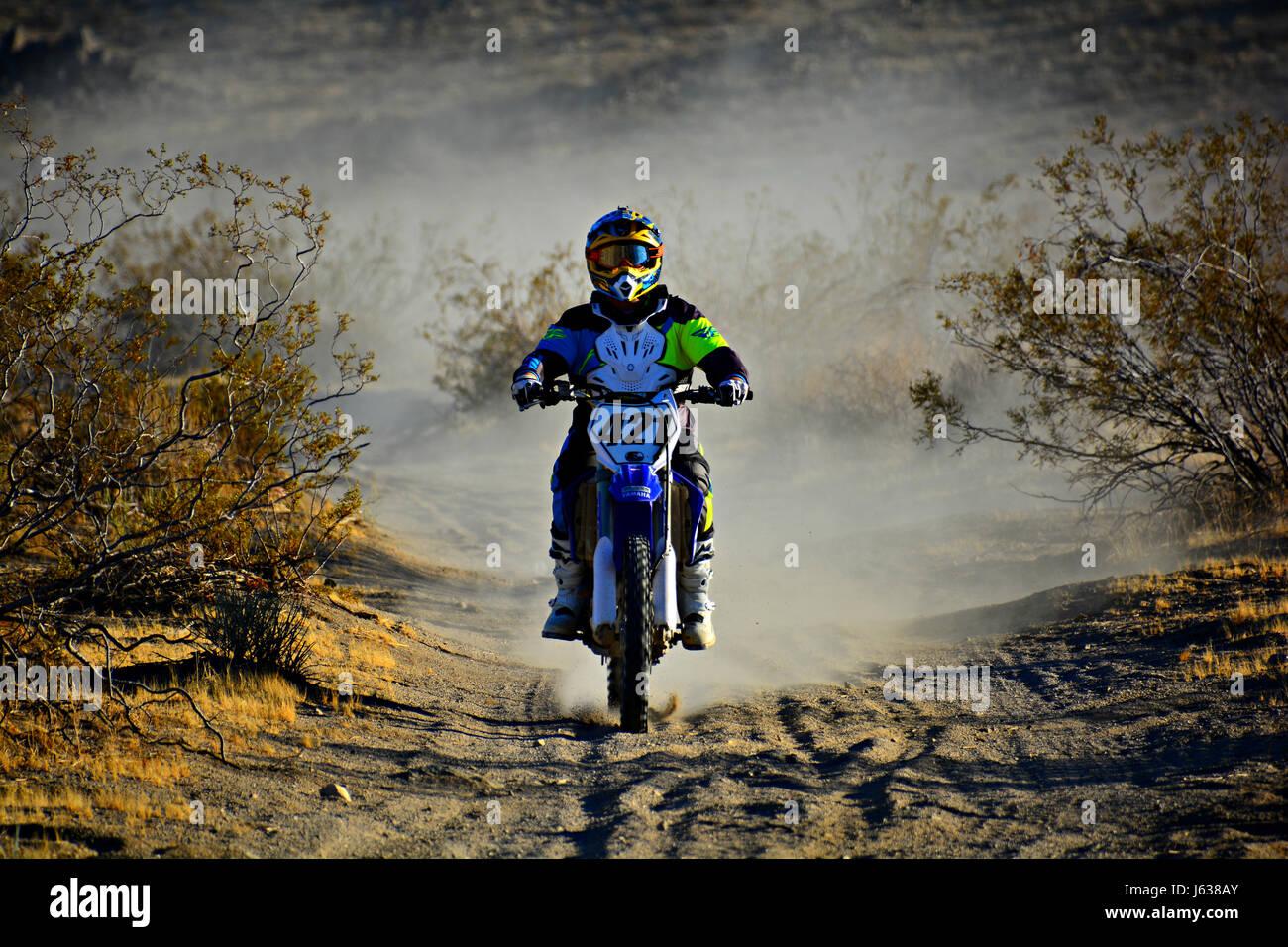 Dirt bike in a cloud of dust speeding through the desert. - Stock Image