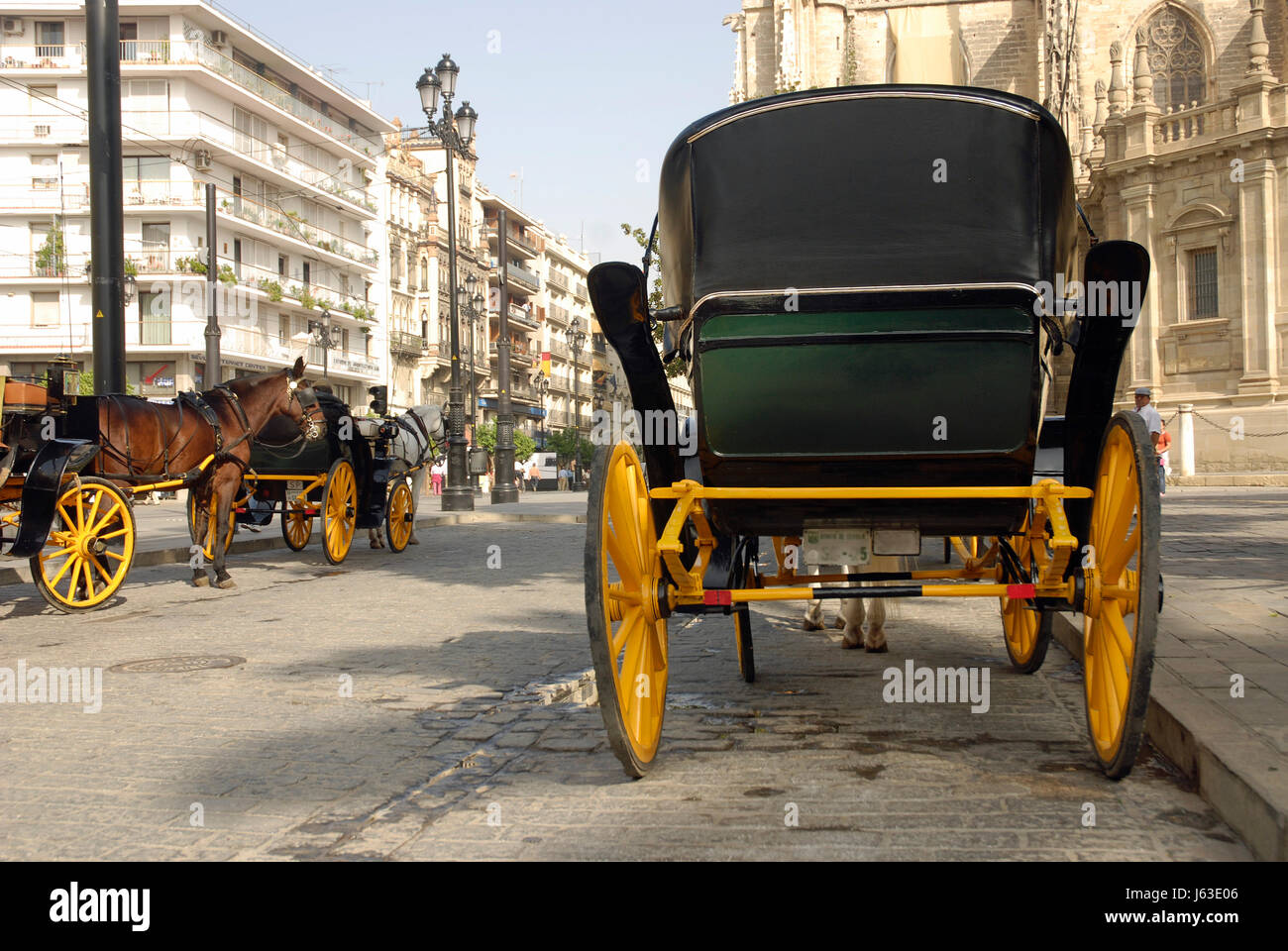 coach seville coaches horse-drawn carriage houses city town holiday vacation - Stock Image