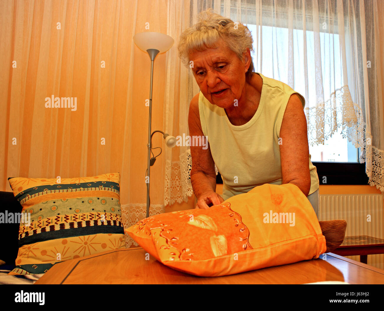 woman at home homework refer cushion old livingroom living room woman household - Stock Image