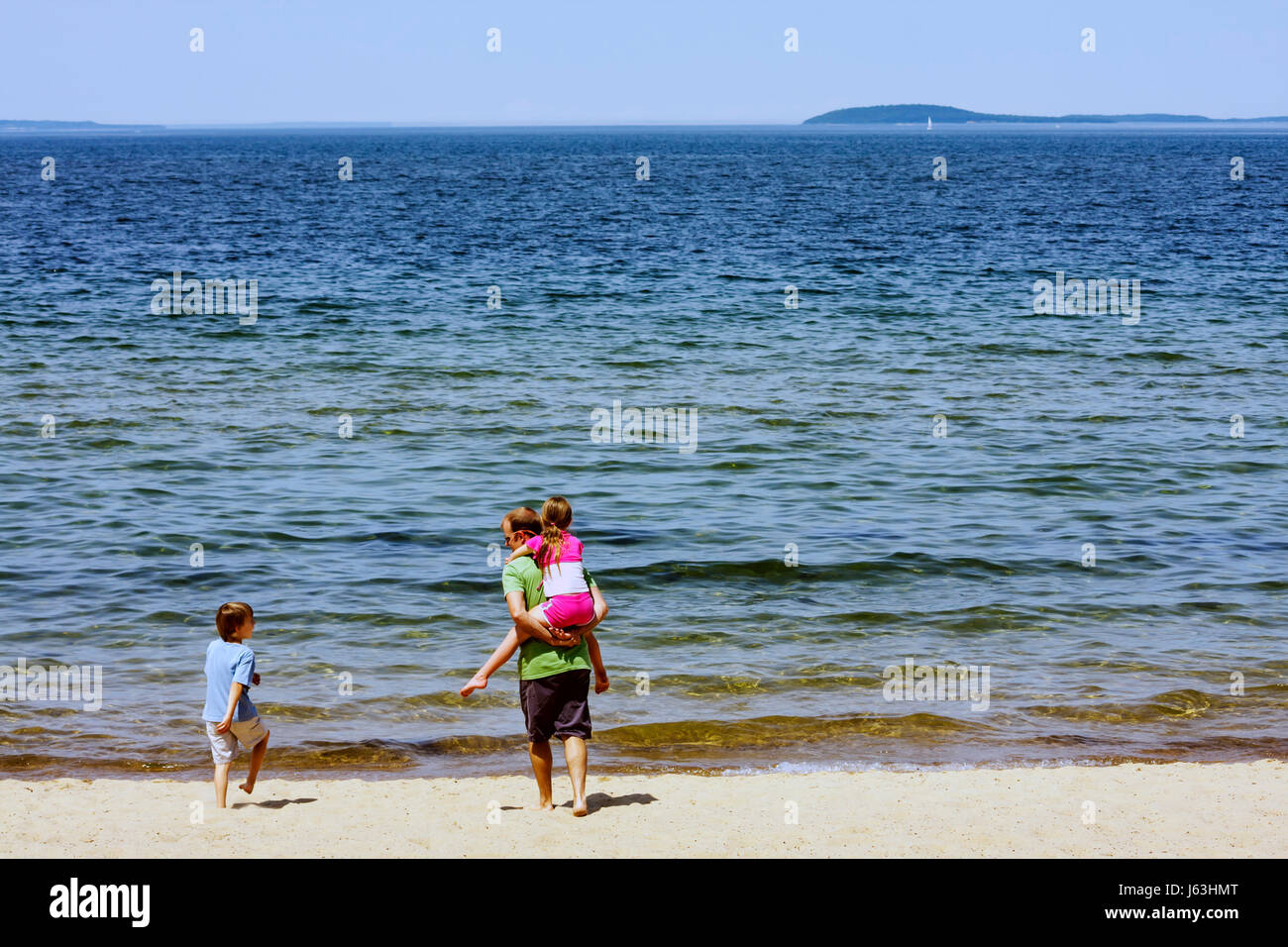 Michigan Traverse City West Arm Grand Traverse Bay Clinch Park man boy girl parent child water beach piggyback play - Stock Image
