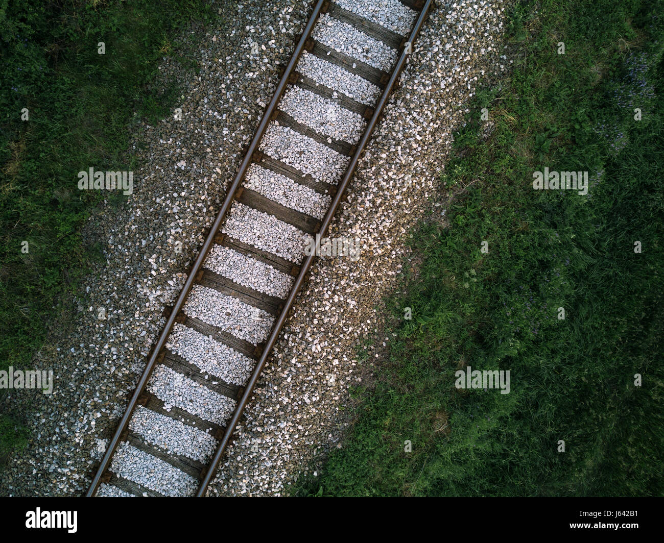 Aerial view of railway track through countryside, drone top view pov of rails as abstract background - Stock Image