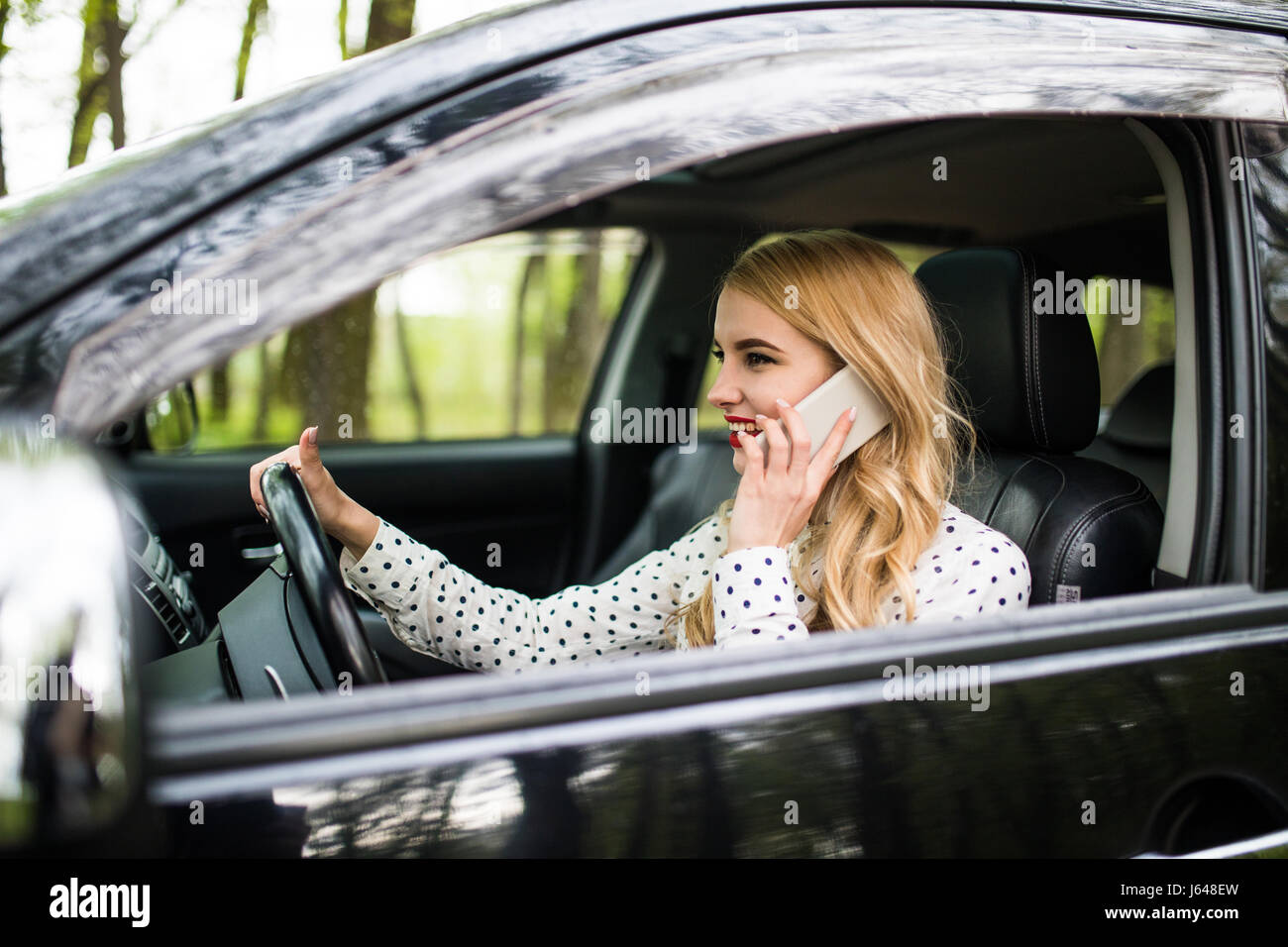 Beautiful business woman is talking on the mobile phone and smiling while sitting in the car - Stock Image