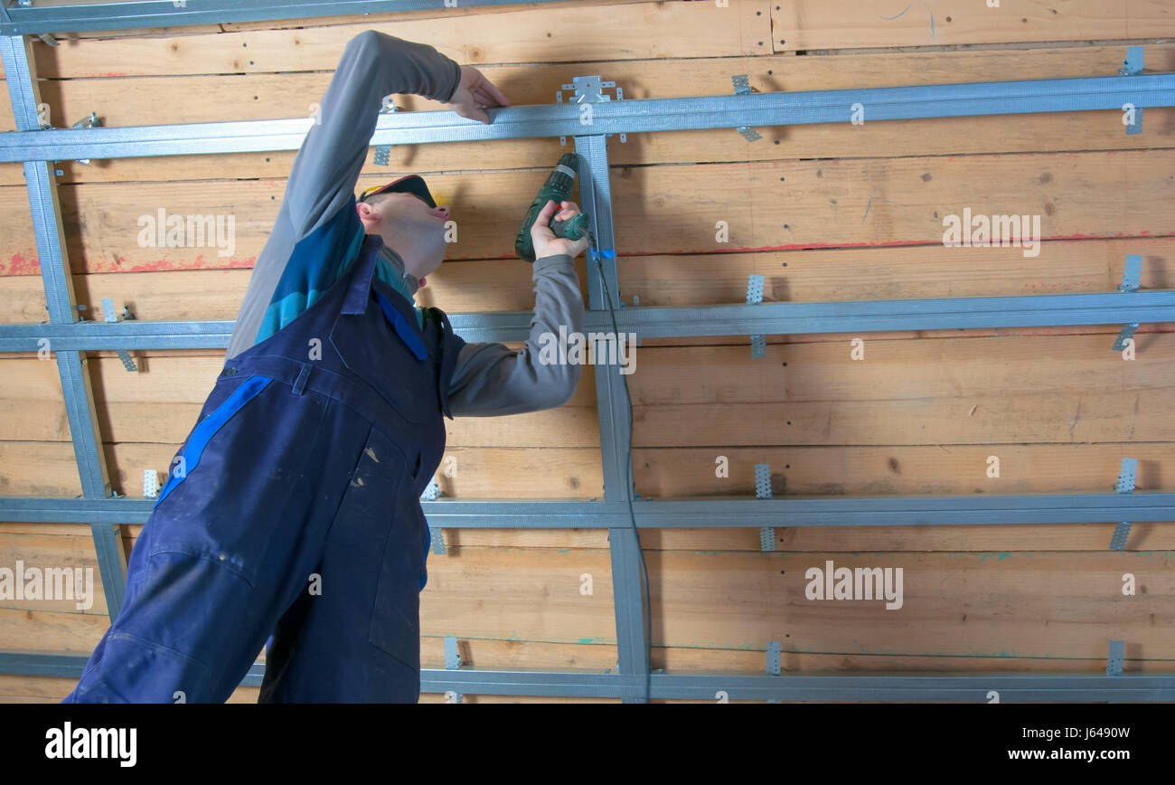 man assembles profile metal frame for plasterboard ceilings Stock ...