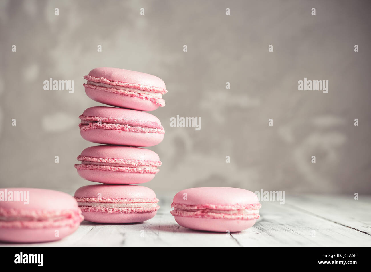 Stack of Raspberry pastel pink Macarons or Macaroons over grey concrete wall background - Stock Image