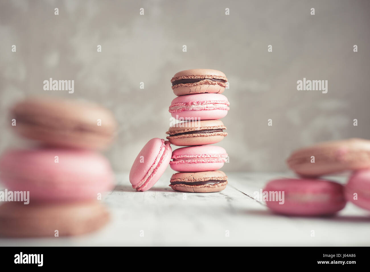 Raspberry and Chocolate pastel colored Macarons or Macaroons over concrete stone background - Stock Image