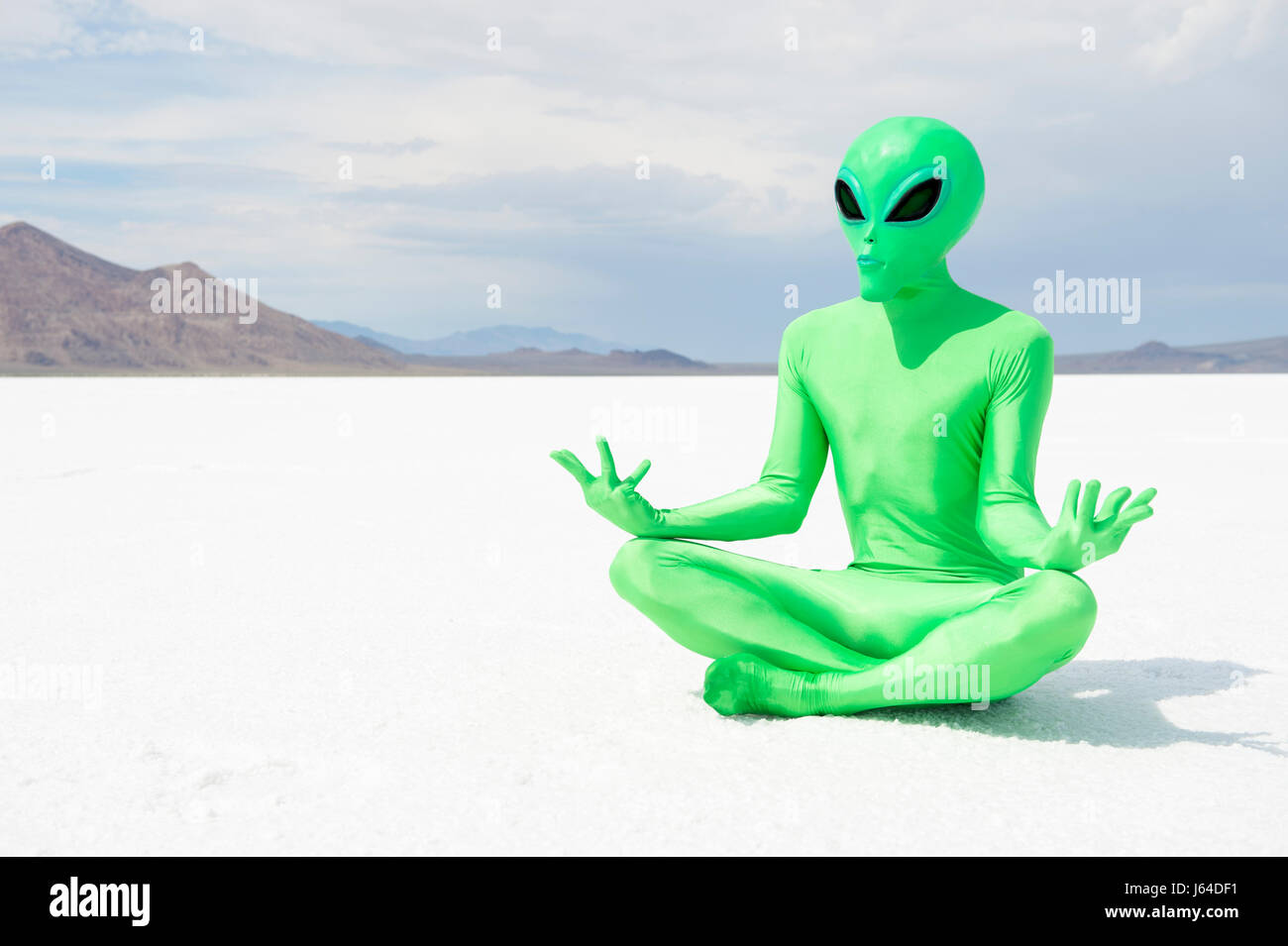 Green alien practicing transcendental meditation sitting in a lotus position on a stark otherworldly Martian desert - Stock Image