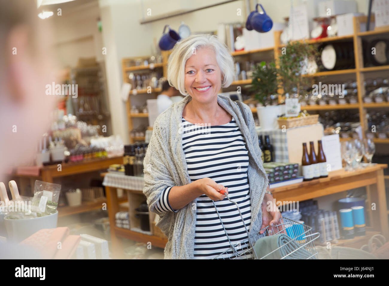 Smiling mature female shopper with basket nearing checkout counter - Stock Image