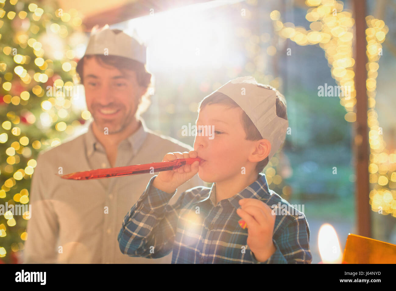 464b9924b4c42 Father and son wearing Christmas paper crowns and blowing party favor