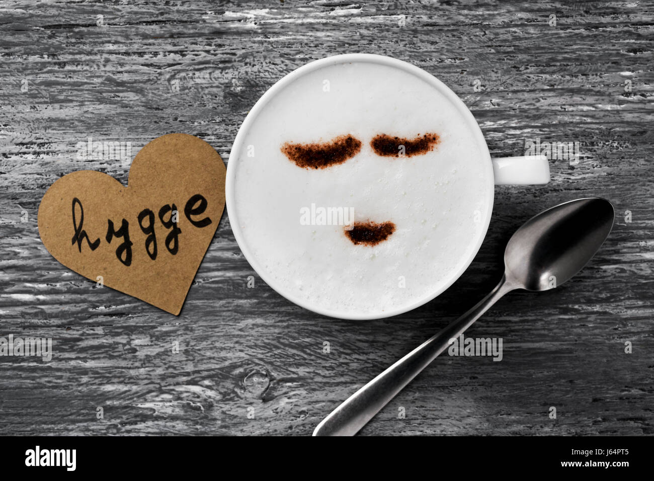 high-angle shot of a cup of cappuccino with a happy face drawn with cocoa powder and a signboard with the text hygge, - Stock Image