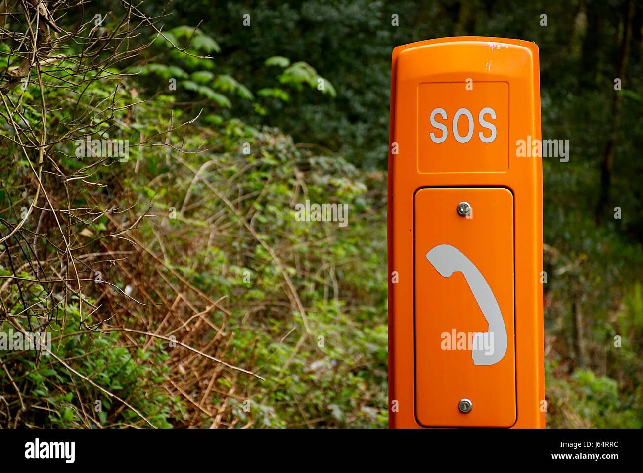 Emergency phone in rural location.North Wales,United Kingdom.Roadside assistance phone.Orange emergency phone box - Stock Image