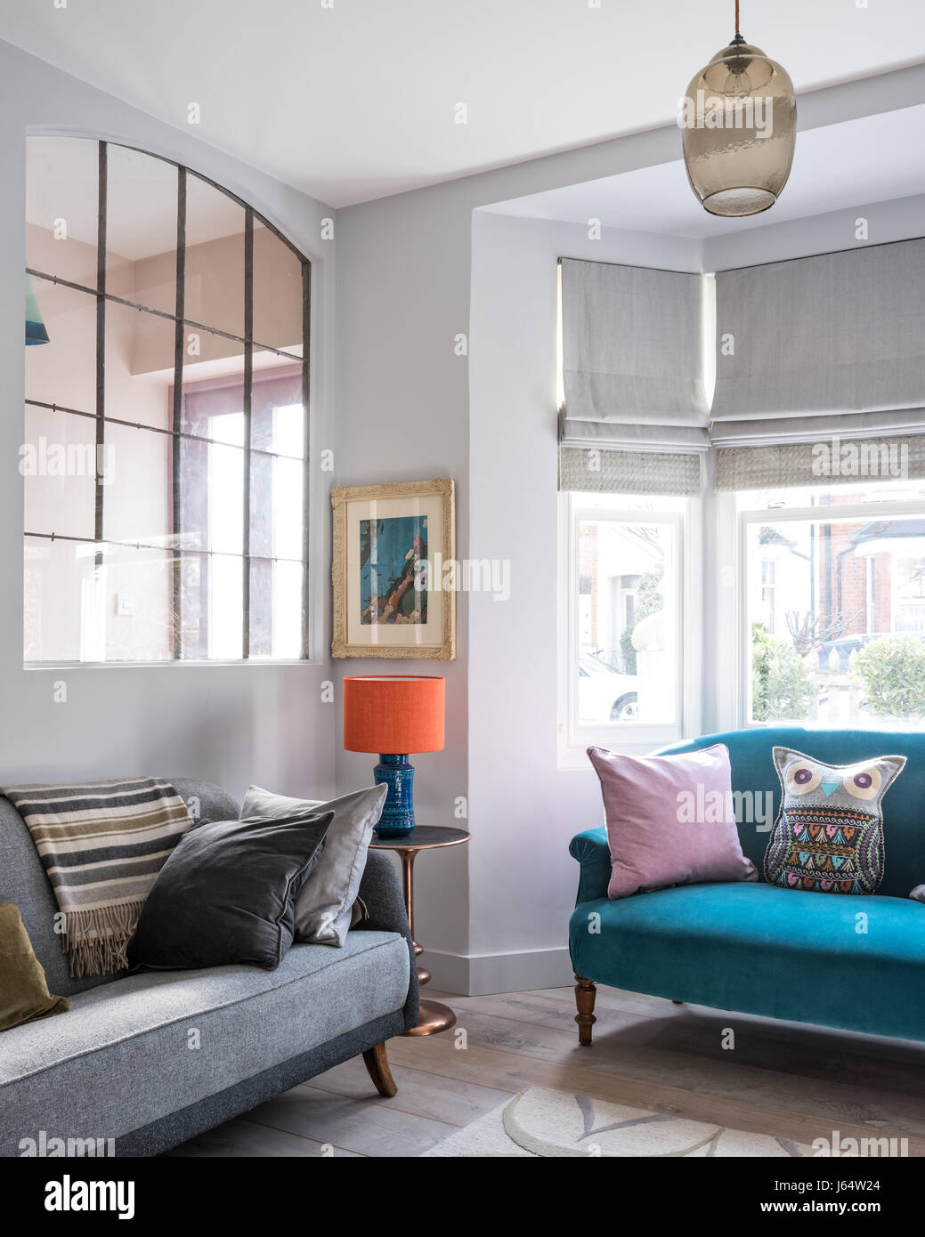 Large french metal salvaged windows in sitting room with grey vintage sofa from French Affair. The rug is by Allegra Stock Photo
