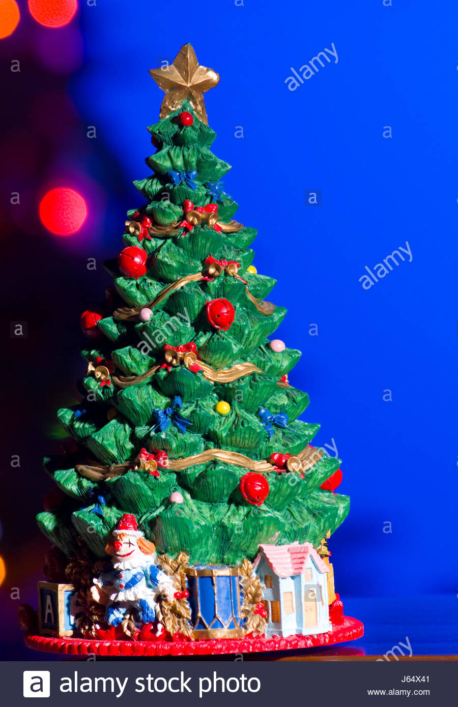 figurine of an evergreen christmas tree and presents set in front of christmas tree with lights - An Evergreen Christmas