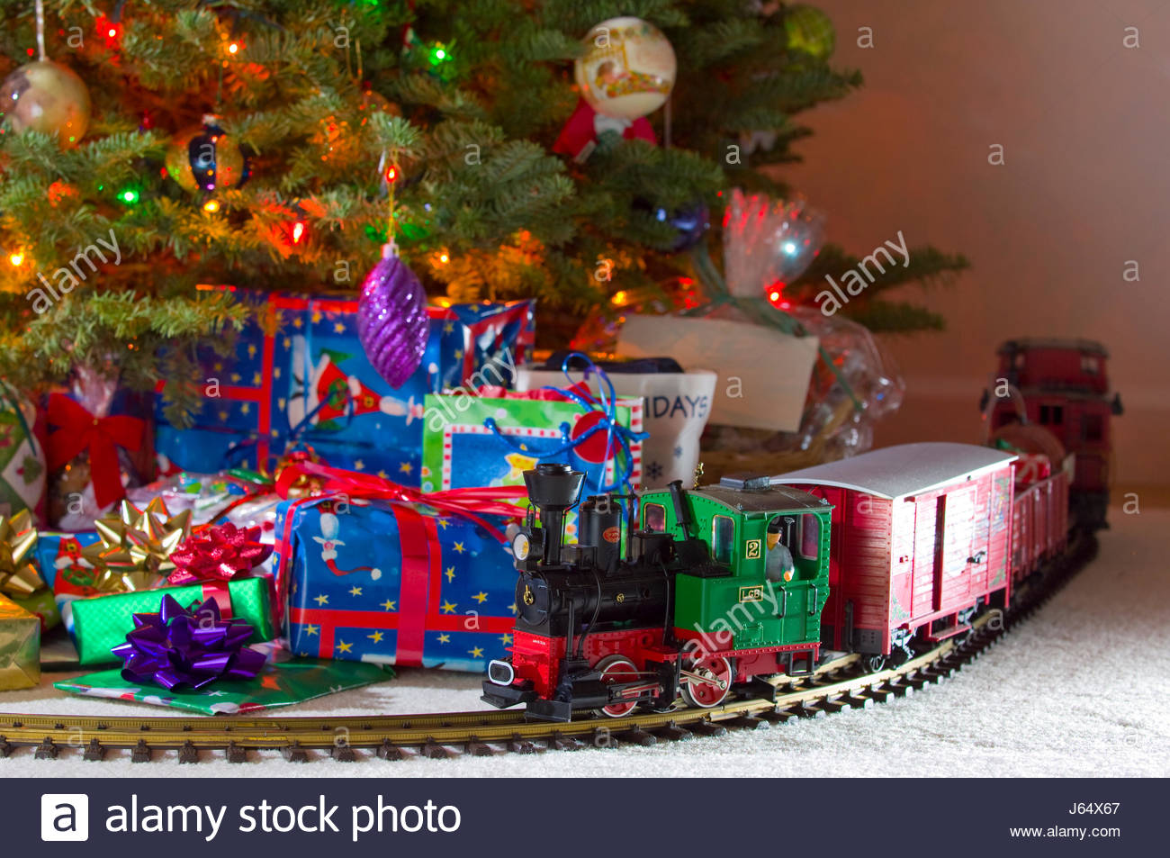 Christmas Tree Train.Toy Electronic Train On Track In Front Of Decorated