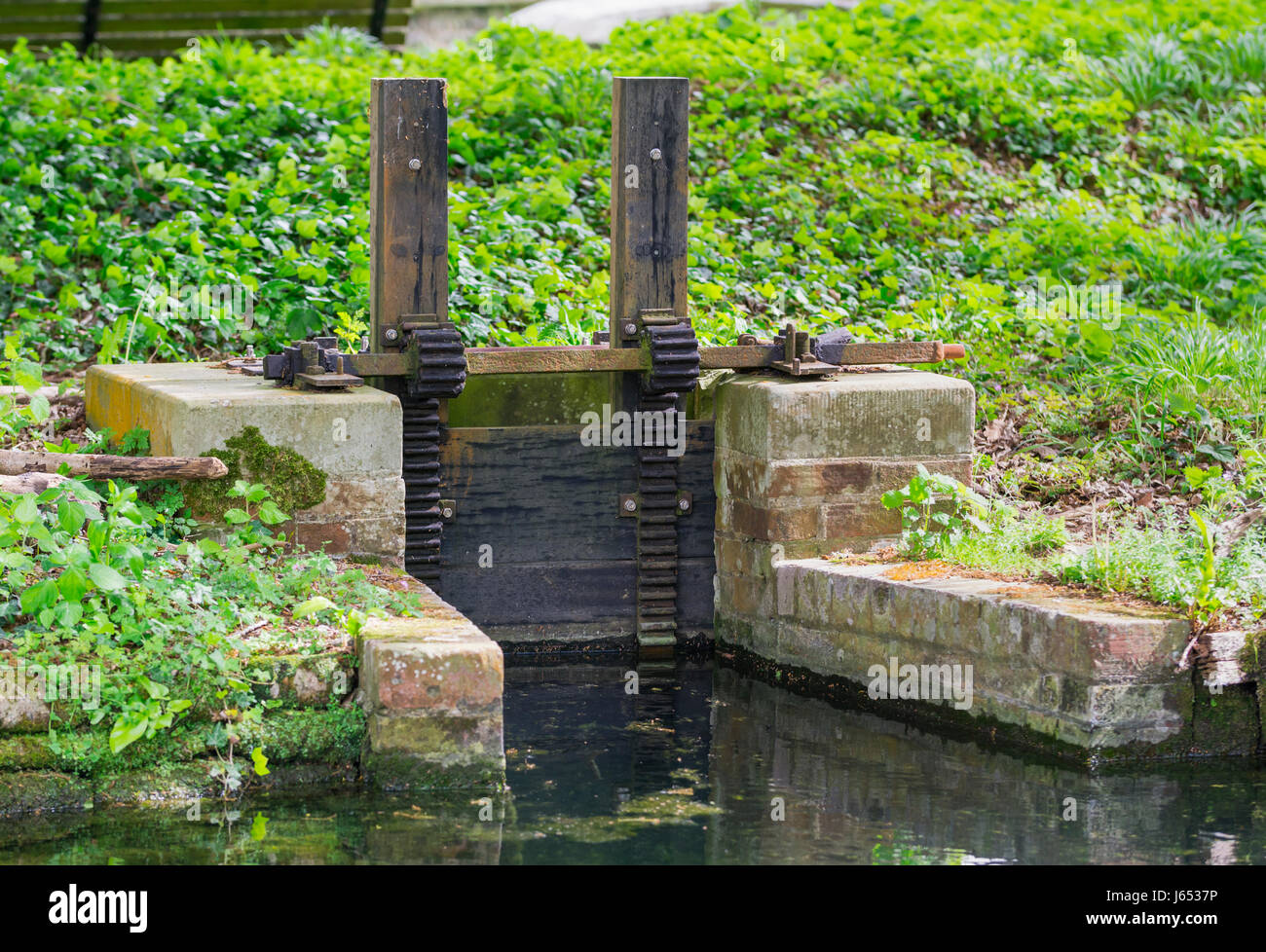 Sluice gate. Small old water sluice gate in the countryside. - Stock Image