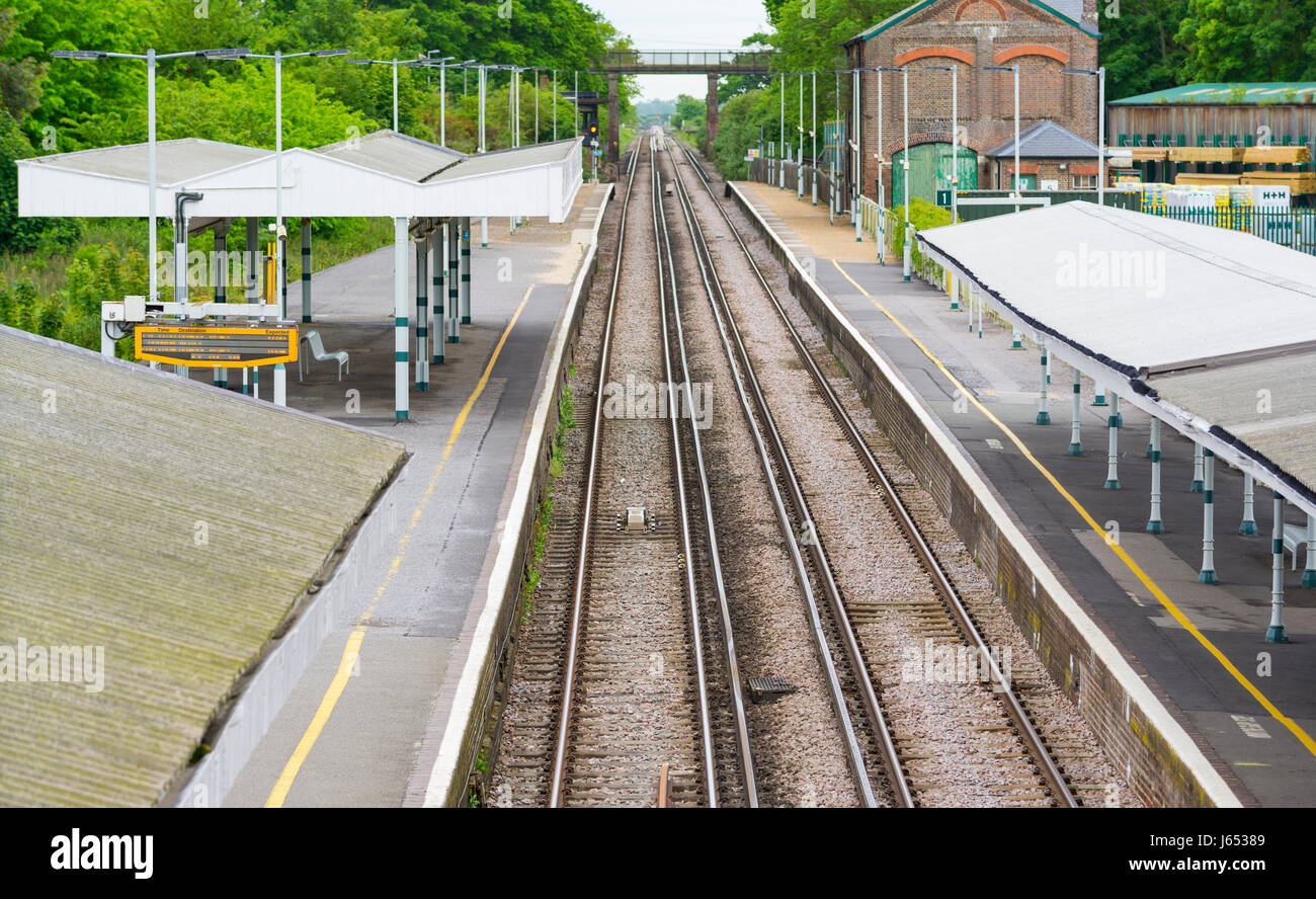 Deserted train station with no passengers waiting and no trains in sight, in West Sussex, UK. - Stock Image