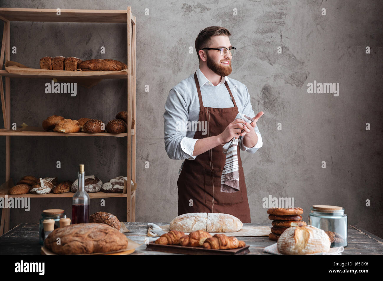 Picture of young happy bearded man wearing glasses baker standing near a lot of bread. Looking aside. Stock Photo