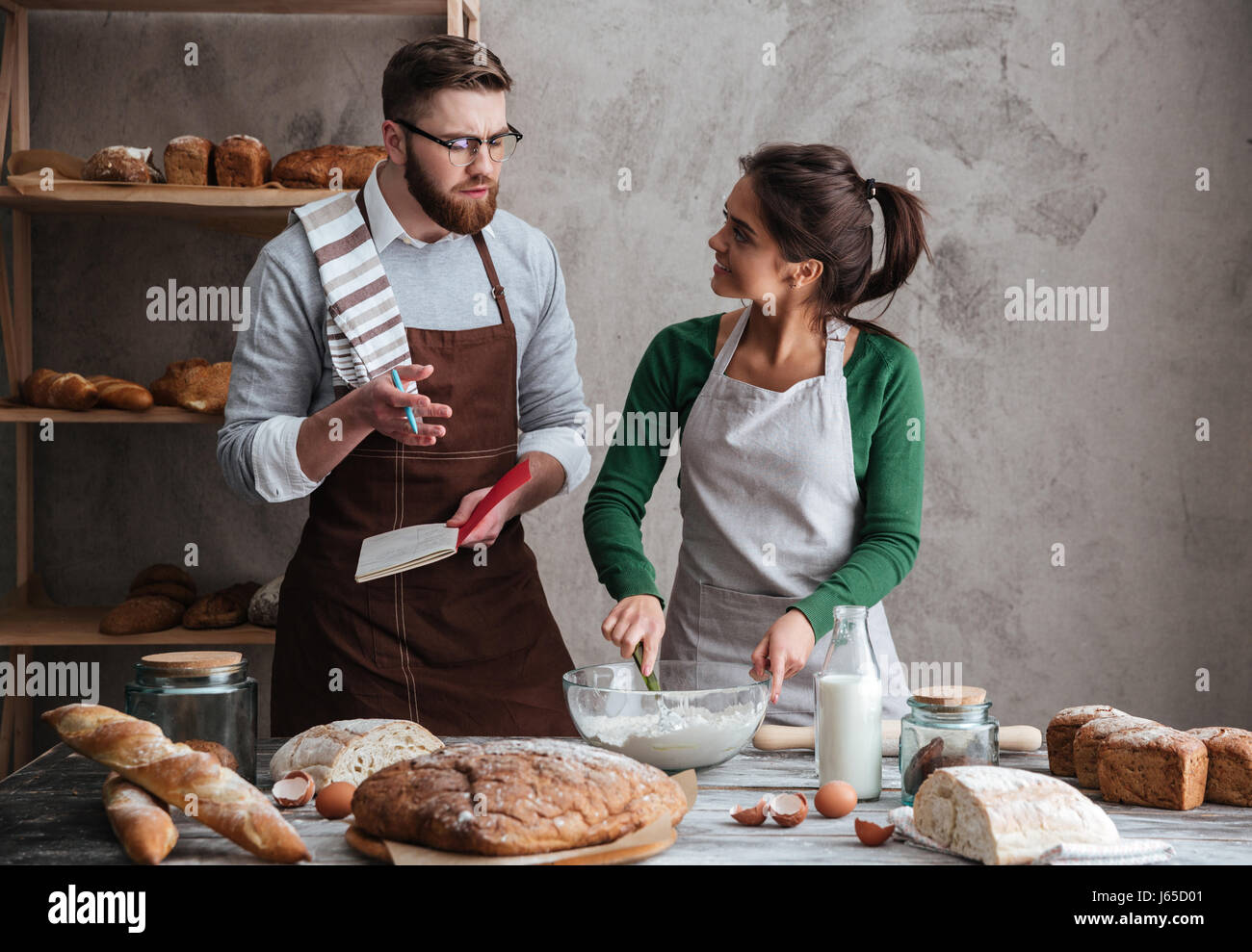 Woman in apron listening her bearded husband while kneading dough Stock Photo