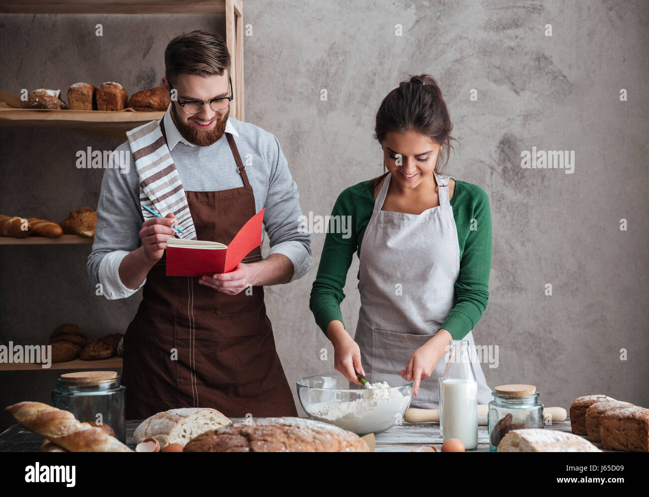 Young smiling woman under sensitive guidance of her man listening recipe of bread and cooking it in kitchen Stock Photo