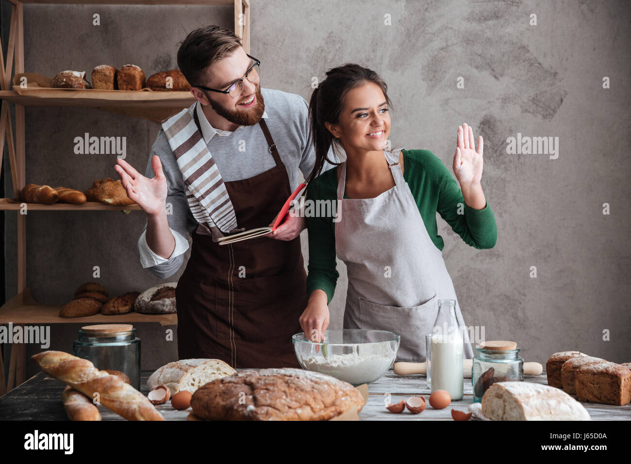 Happy couple looking away wile cooking bread and greeting with someone - Stock Image