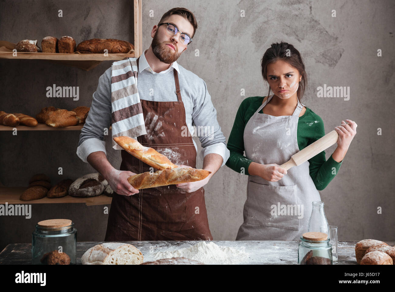 Young man with two loafs and woman with rollin pin standing in kitchen earnestly Stock Photo