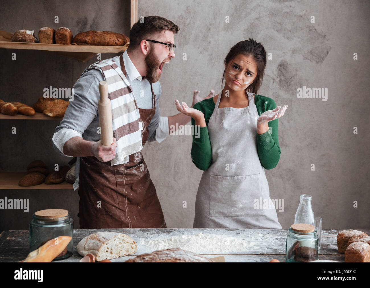 Angry bearded man in glasses shouting at his woman in apron while they cooking in kitchen Stock Photo
