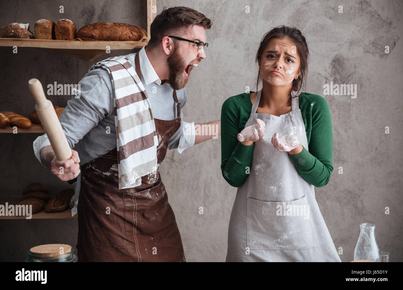 Angry bearded man in glasses shouting at his woan in apron while they cooking in kitchen Stock Photo