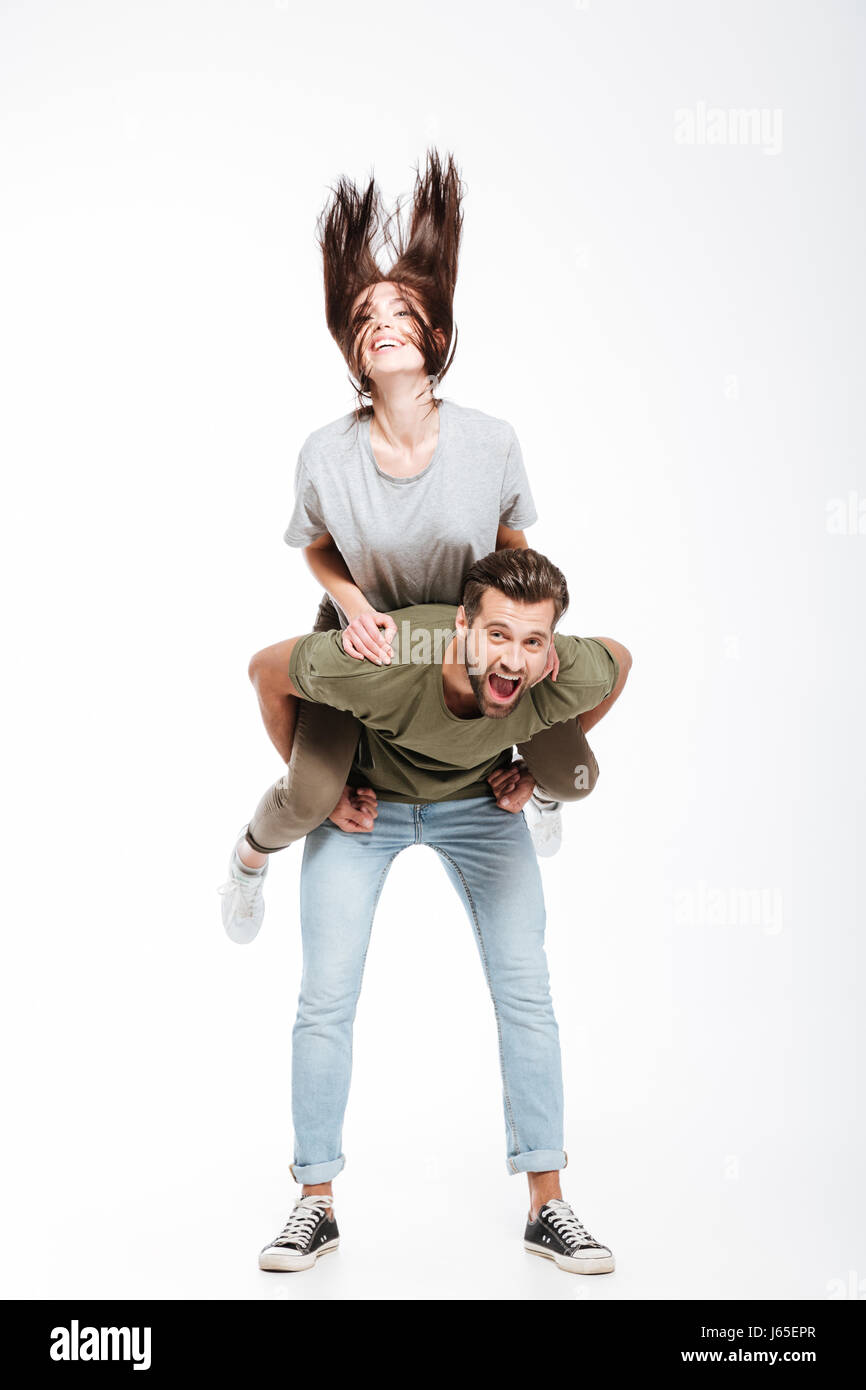 Happy couple having fun. Woman shaking her hair while sitting on man' back isolated - Stock Image
