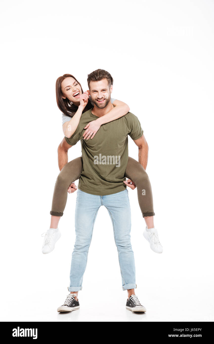 Brunette young woman enjoying piggyback ride on her man and touching his face - Stock Image