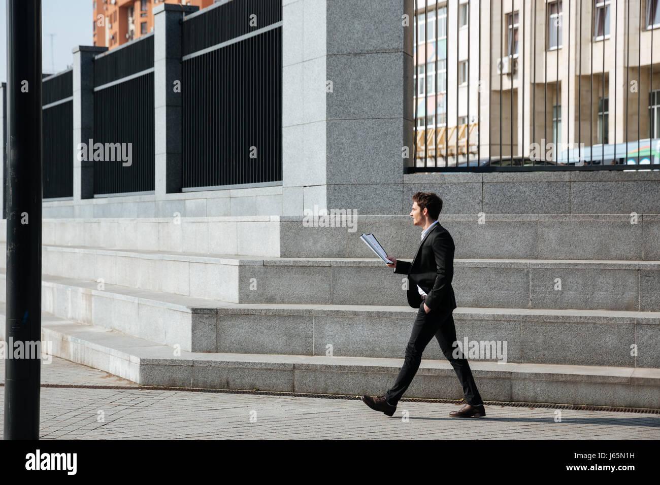 Full-length of businessman holding folder standing near stairs in the sreet - Stock Image