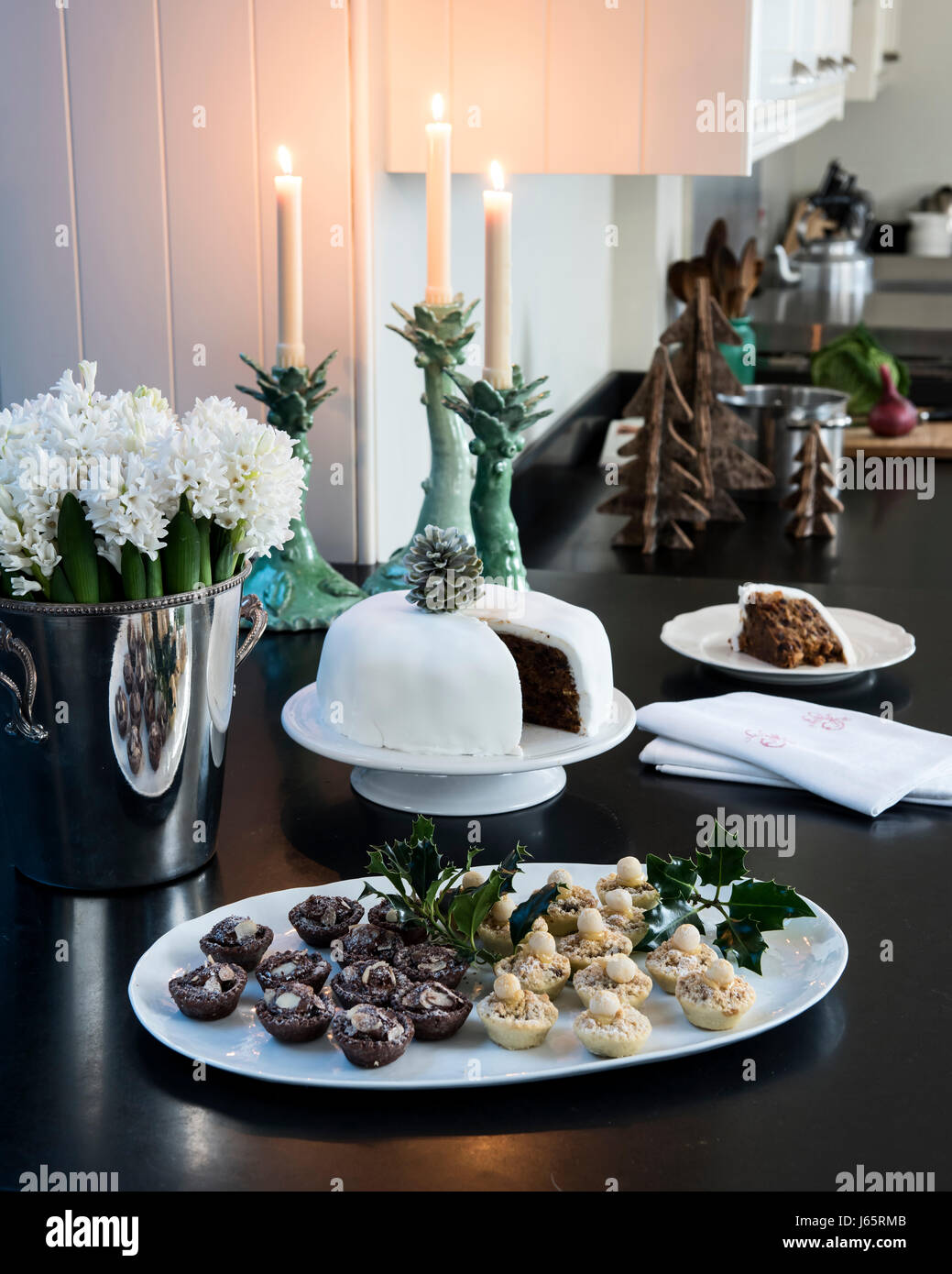 Small tarts and Christmas cake on a black stone worktop in elegant candle-lit kitchen - Stock Image