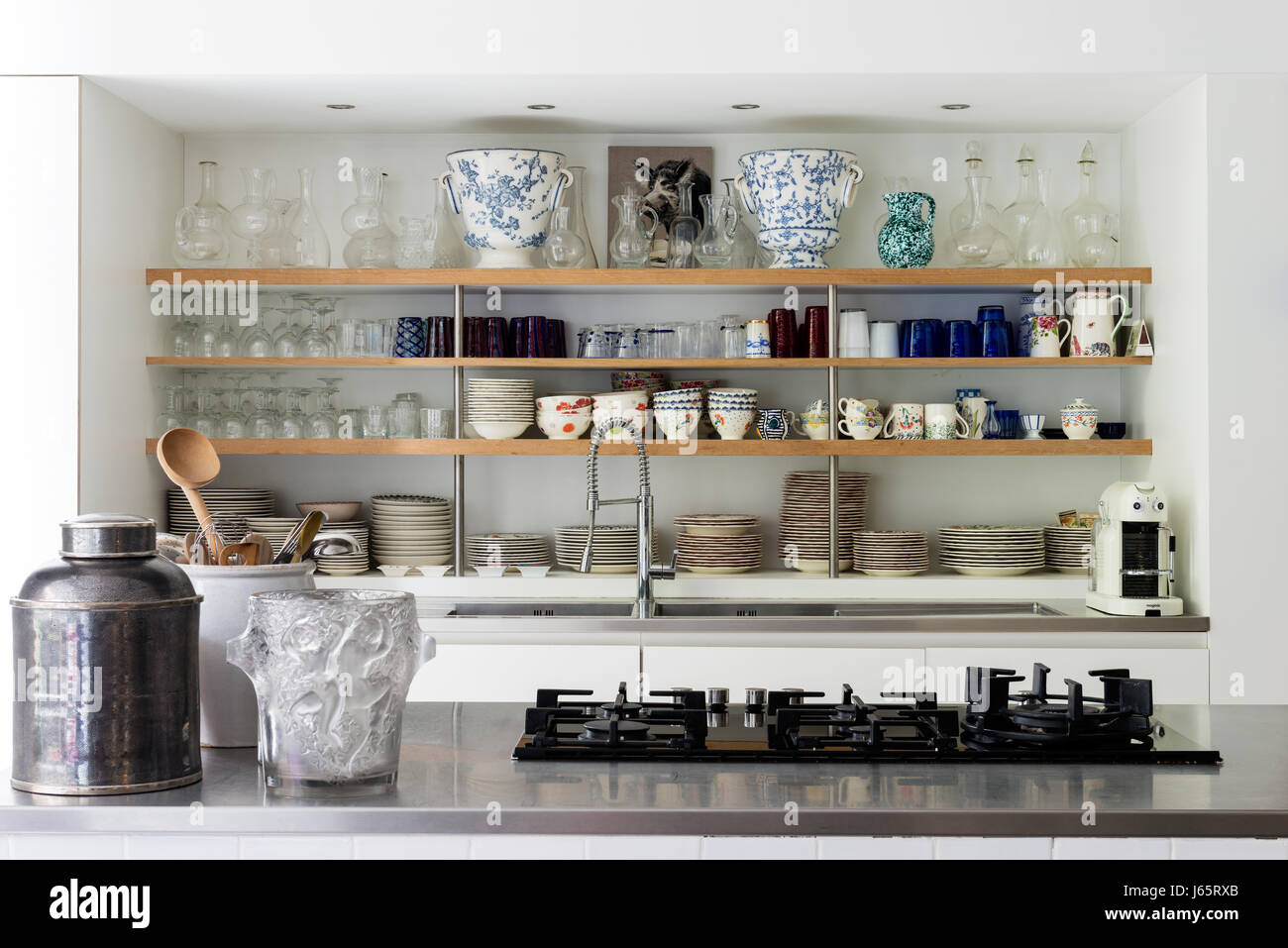 Crockery and glassware storage in kitchen of Brussels atelier with five ring hob - Stock Image