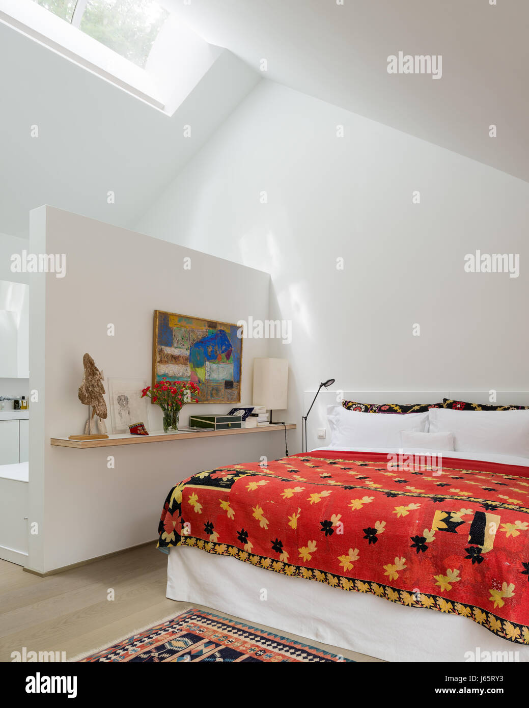 A-frame roof with low diving wall to ensuite and red quilt from Dhaka - Stock Image